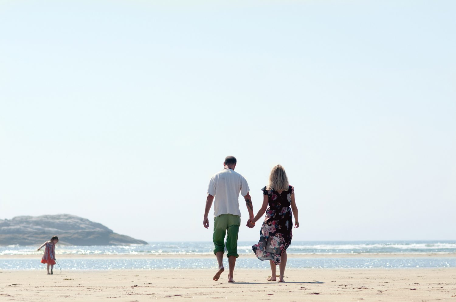 couple walking on the sandy beach holding hands