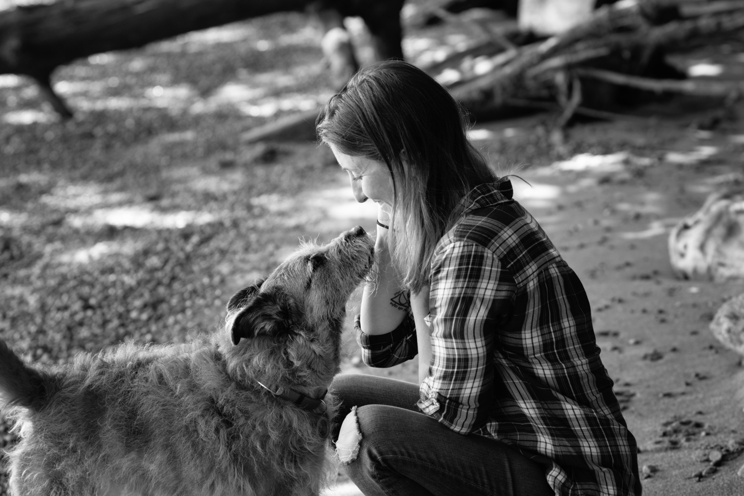 Black and white photograph of woman and her dog looking at each other on the beach