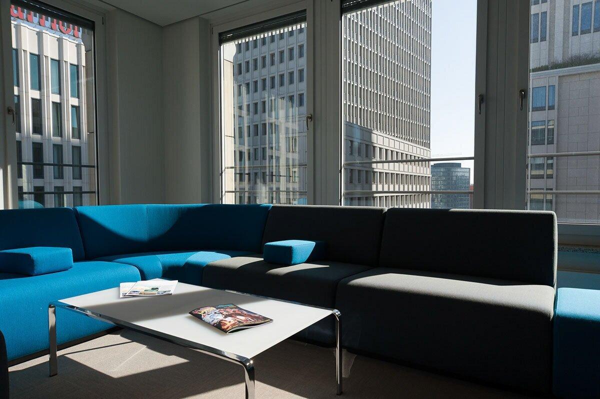 Foto des Interior für eine internationale Anwaltskanzlei in Berlin. Das Bild zeigt die Aussicht auf den Potsdamer Platz und Designermöbel entsprechend der Firmen Farbe.