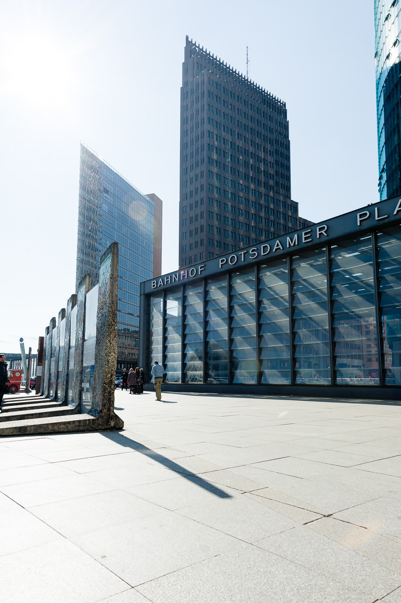 Der Bahnhof Potsdamer Platz mit Stücken der Berliner Mauer im Vordergrund mit Sicht auf den Kolhoff Tower und den Deutsche Bahn Turm am Sony Center.