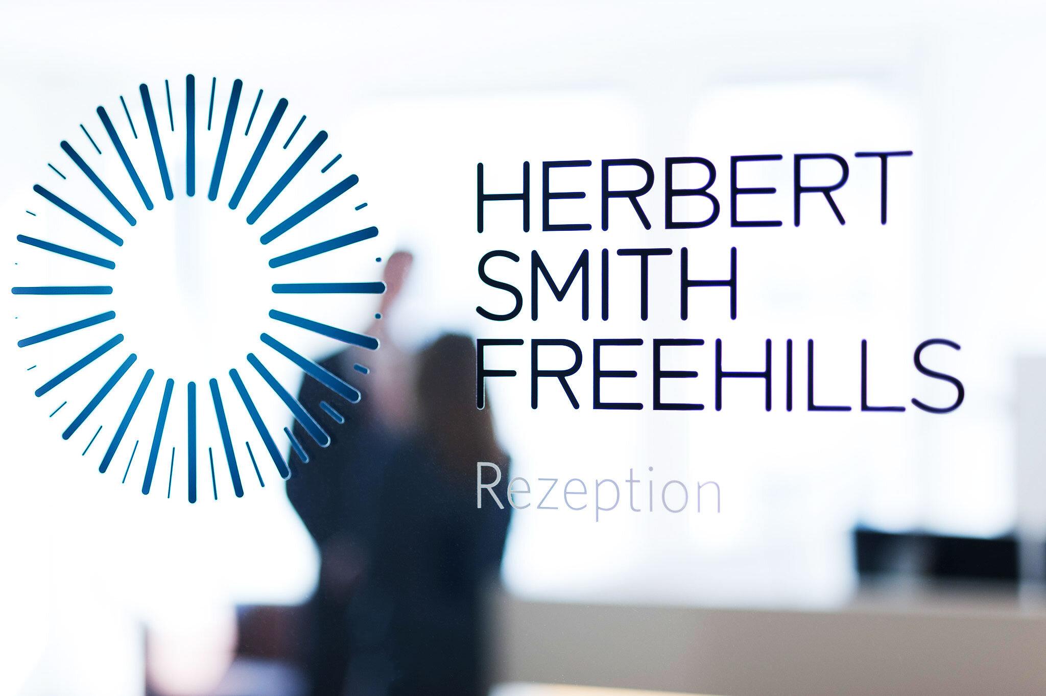 Blick durch die Glascheibe der Rezeption der Kanzlei HSF am Standort Berlin mit Personen in der Unschärfe.