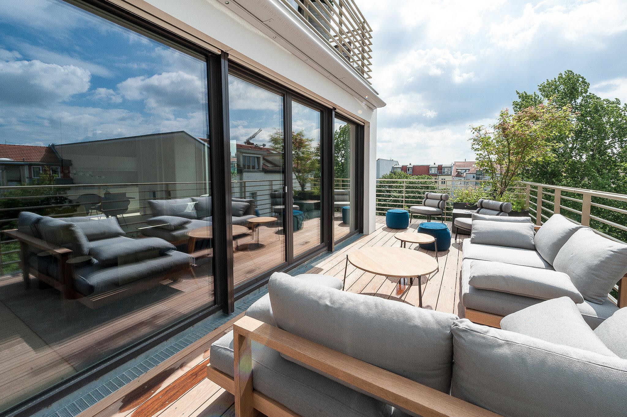 Balkon eines Luxusapartments im Sonnenschein mit Sitzmöbeln und