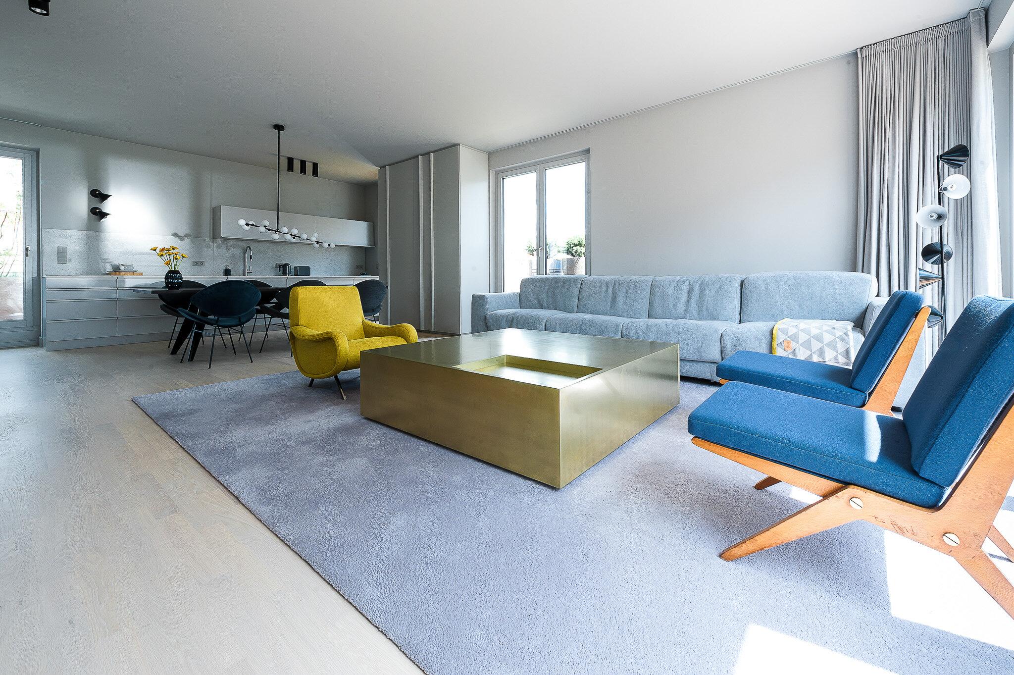 Wohnzimmer im Apartment mit Designermöbeln und offener Küche