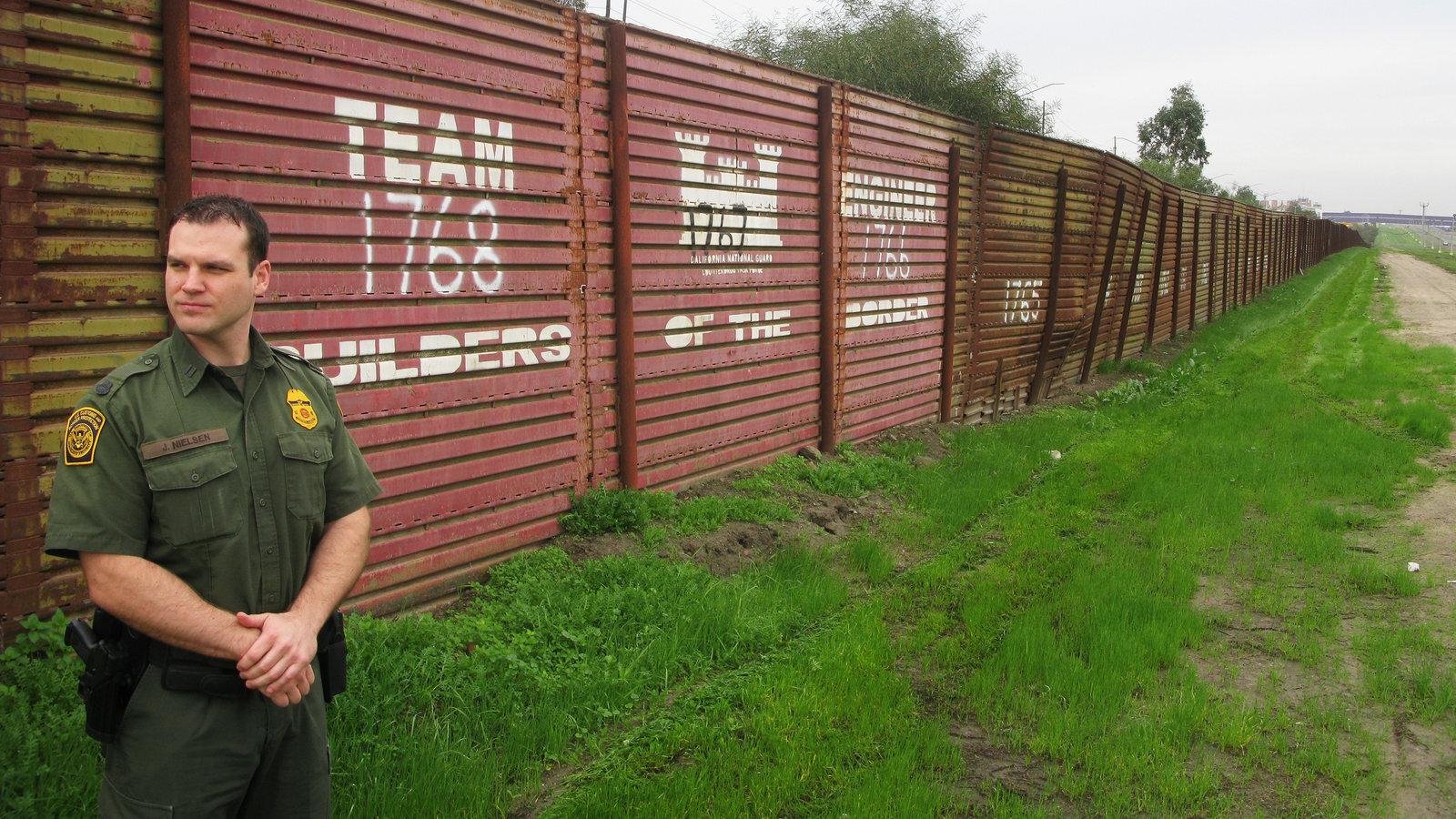 Border Patrol agent James Nielsen stands near the original Vietnam-era landing-mat border fence near Chula Vista, Calif. Credit:  NPR