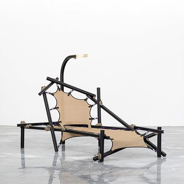 """The Angler Chaise Lounge by Arcana Aluminum, Trampoline Fabric, Springs, Acrylic, Bronze 40 x 68 x 52 $18,000 • The Angler Chaise Lounge is a culmination of misused materials and misapplied techniques. A tangled nest of 80/20 extruded aluminum with cast brass connectors provide the framework for this unapologetically confident piece. Arcana then employed trampoline fabric as upholstery to suspend the """"lounger"""" beneath a custom milled acrylic reading lamp. They have completely transformed the traditional chaise lounge through adaptive mis-use of stock materials laying around their studio. • For inquiries/acquisitions, DM or email us: hello@igc.design 📧 • #chaise #chairdesign #collectiblefurniture #conceptualdesign #chairlove #contemporarydesign #collectibledesign #objectdesign #designdetail #seating #designshow #groupshow #luxuryfurniture #interiordesign #modernhome #designstudio #furnituredesigner #moderndesign #designshowroom #designcollection #chairs #fernandomastrangelo #ingoodcompany2019 #arcanawork #igcdesign"""