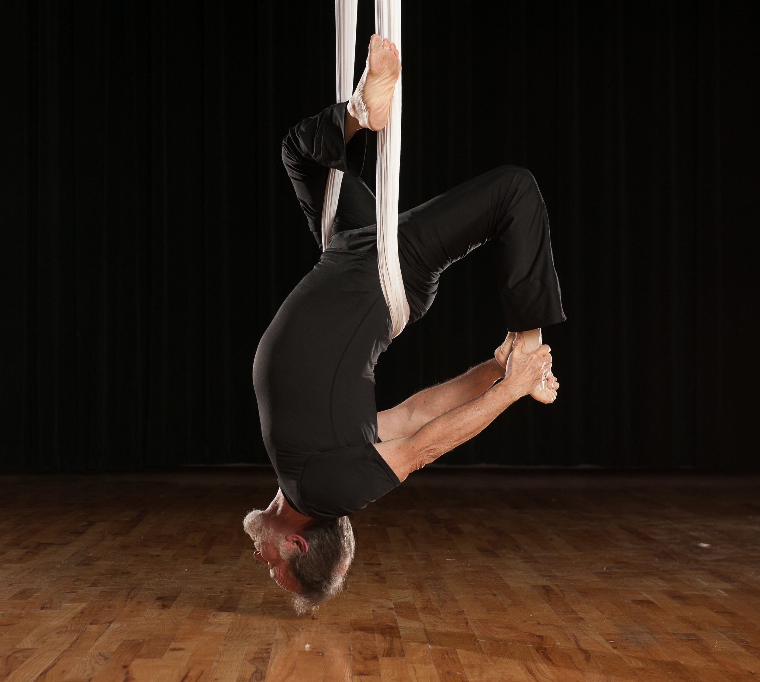 Alex Harrington performing aerial yoga.