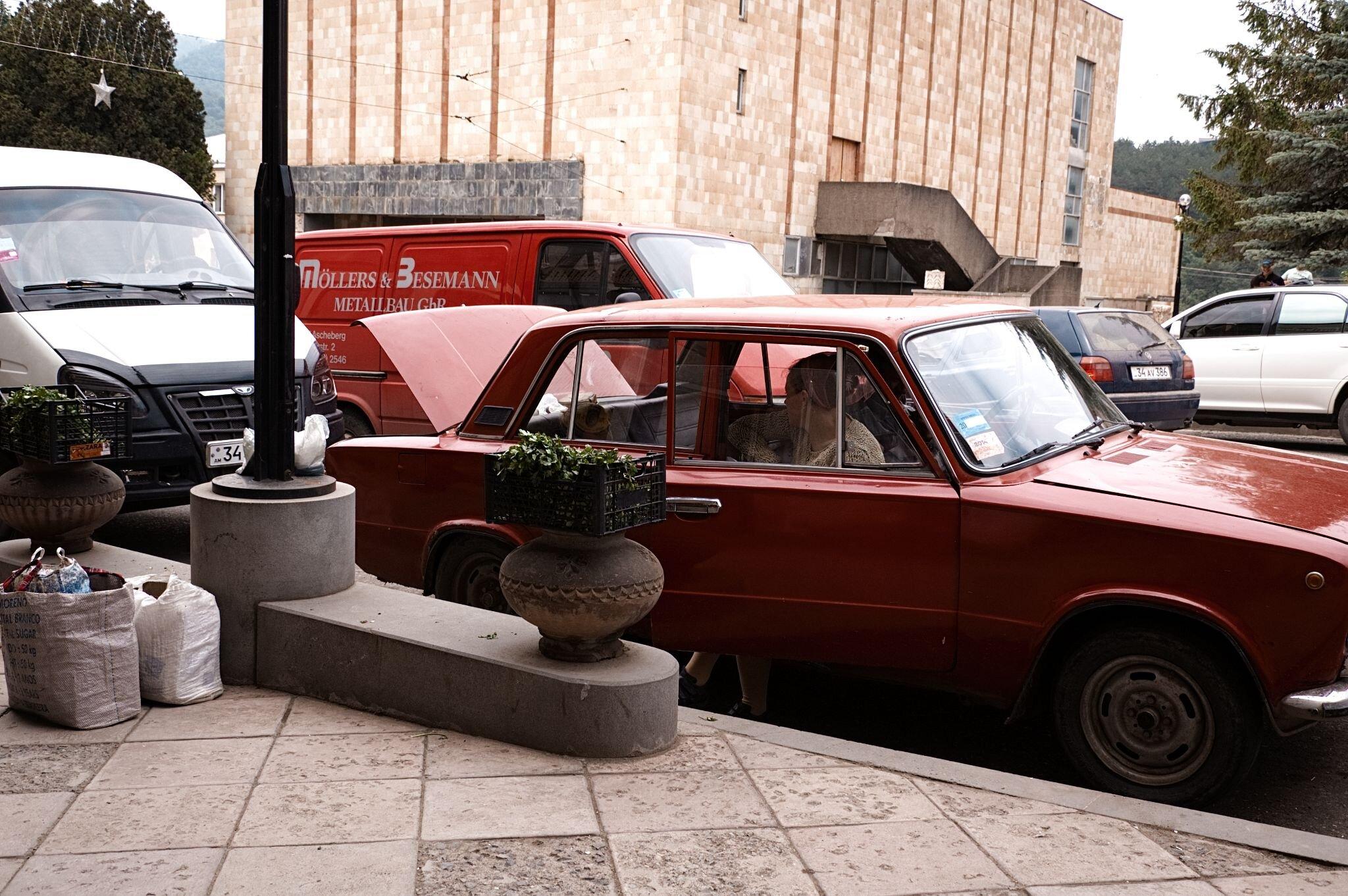 Straßenverkäuferin sitzt in ihrem roten Auto