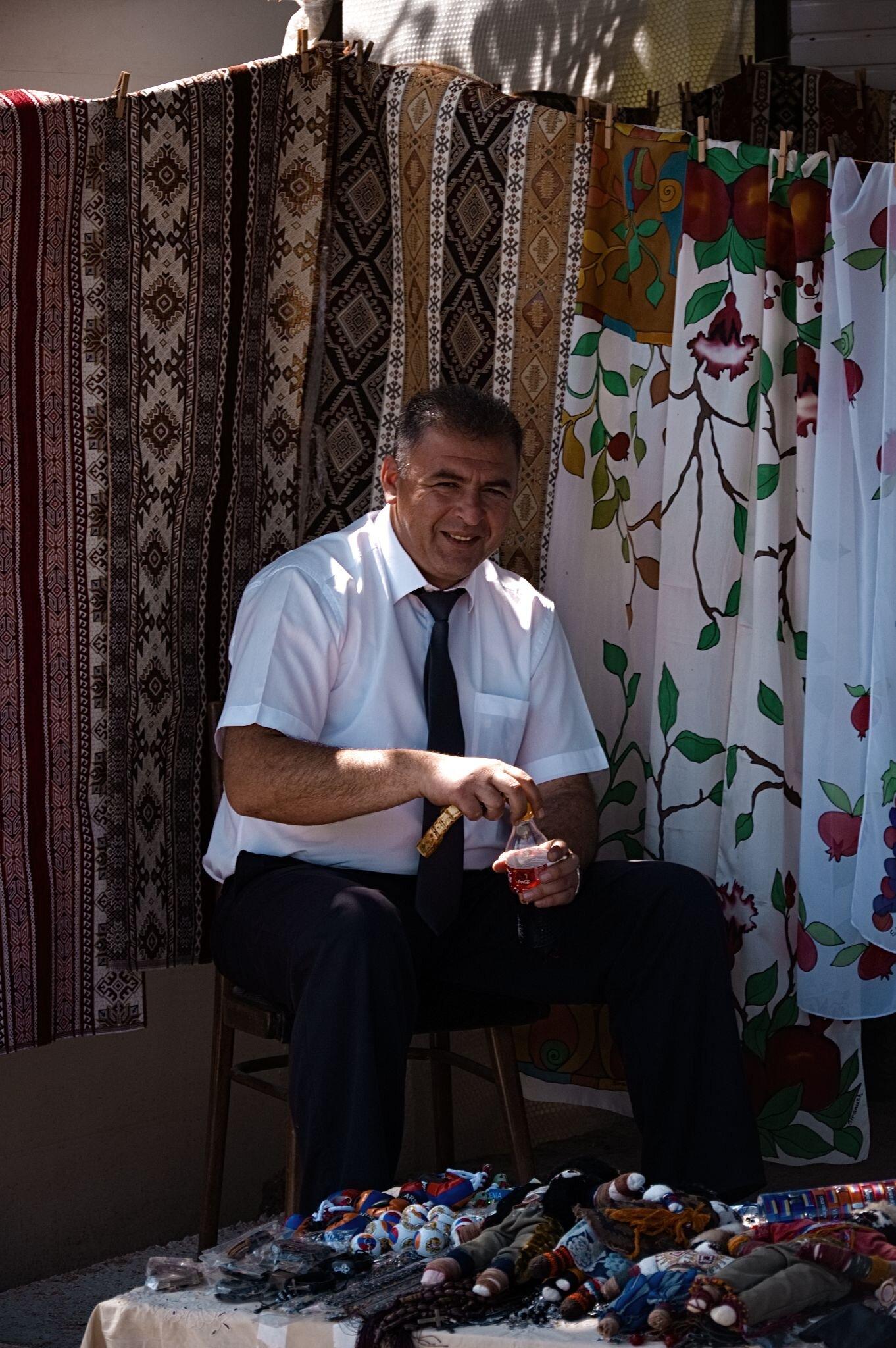 Mann im weißen Hemd vor Tüchern