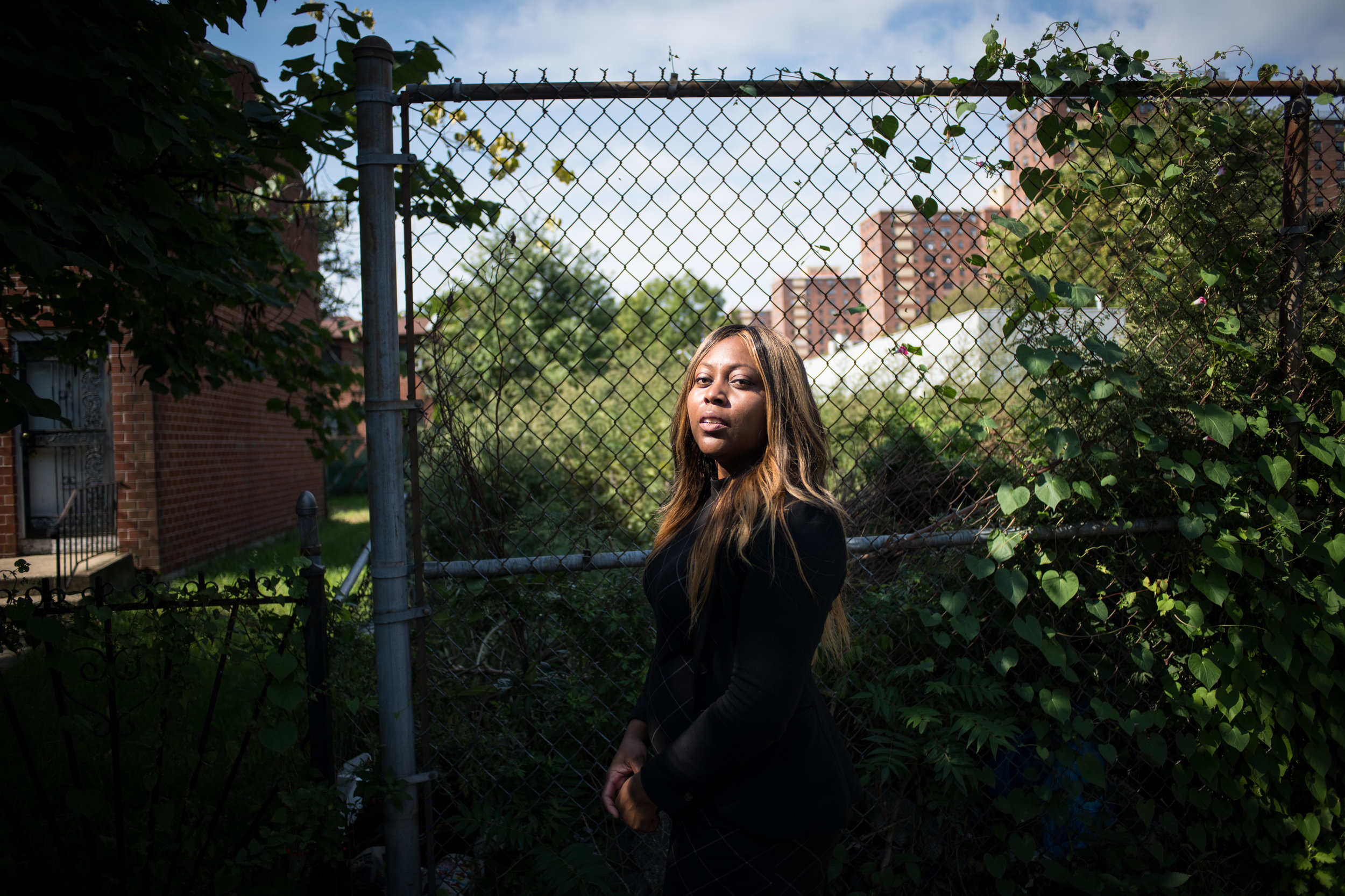 Audra Palacio on Christopher Ave. near her family's home in Brownsville, NY October 2018. As a child, Palacio moved from public housing to the nearby Nehemiah homes—affordable homes that came with cash subsidies from the government. Today, there's a stark economic divide block-by-block between generations going through the Nehemiah homes versus public housing nearby. Photographed for NPR