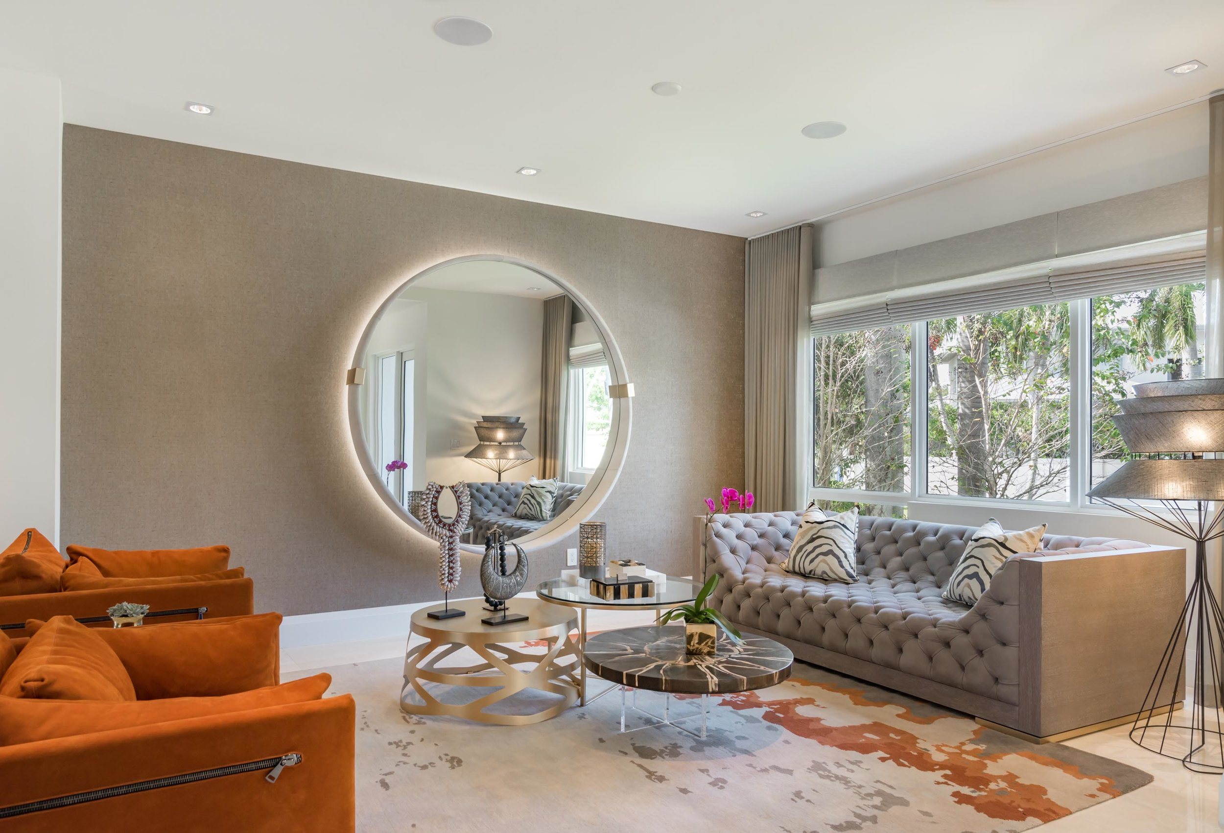 Living room with large round mirror, gray buttoned sofa, brown armchair, round modern style tables and glass window