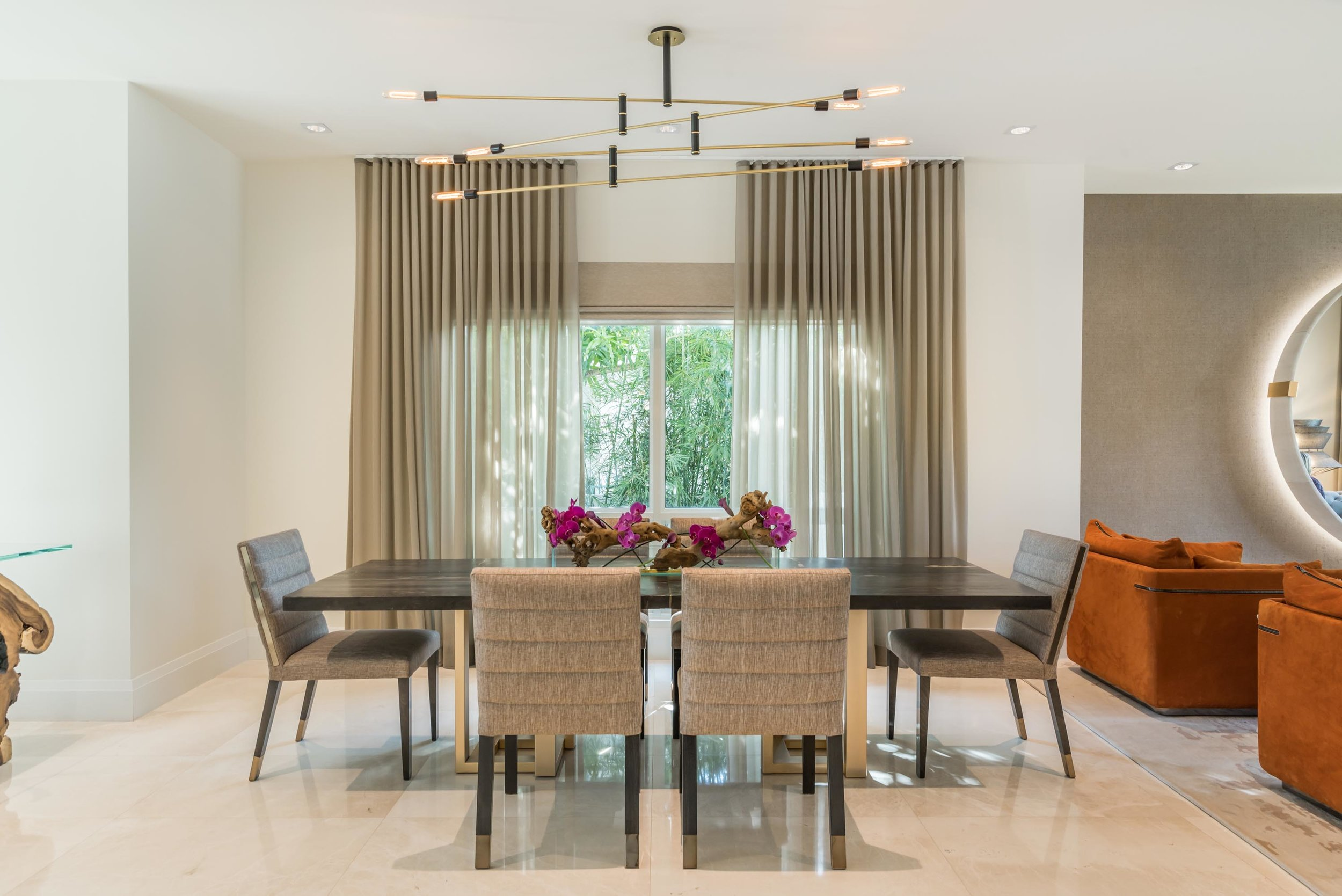 Elegant dining room with wooden table, soft seat chairs, window with curtains and custom chandelier