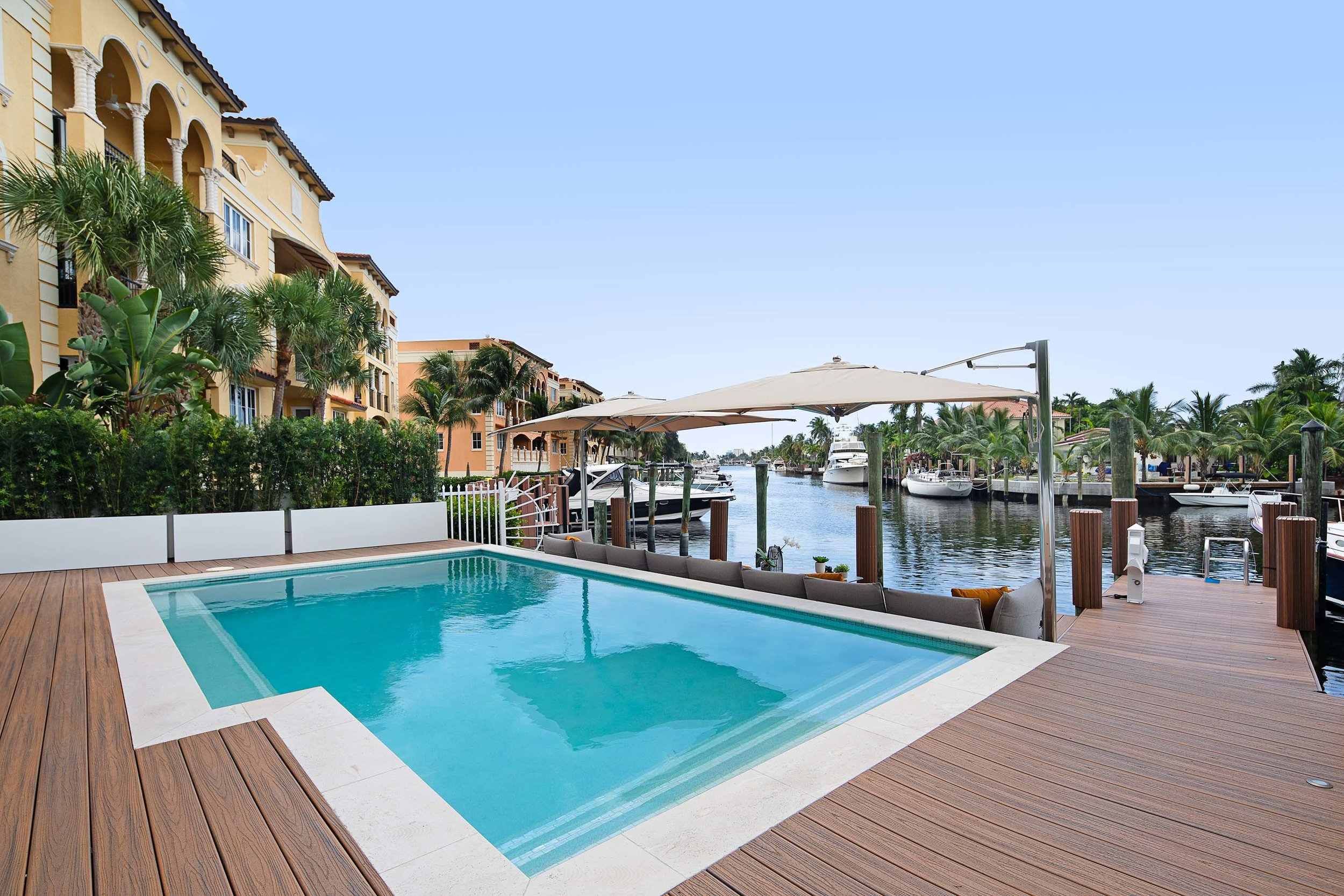Seaside resort pool area with green plants, hardwood floor and canopy