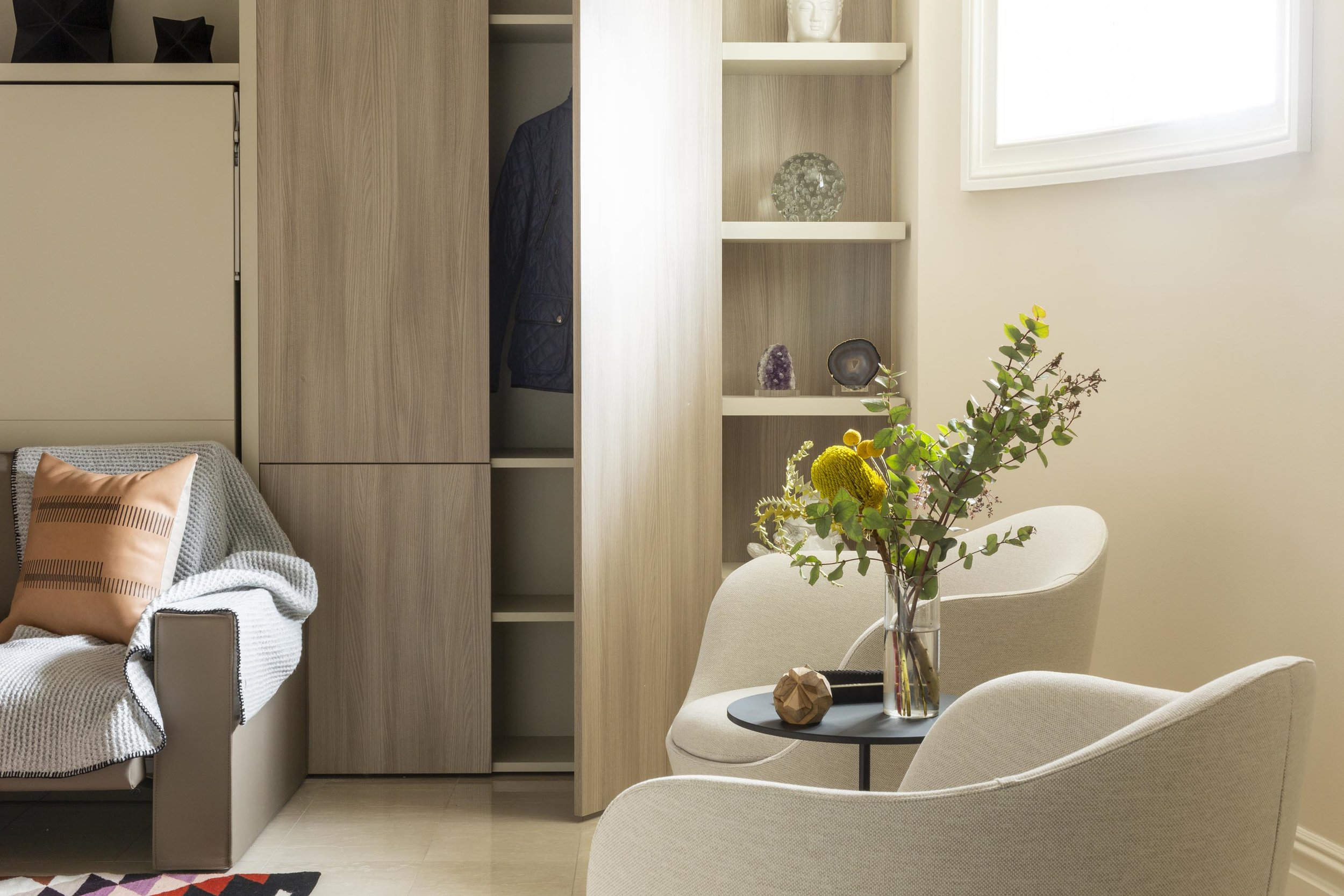 A room with open cabinet, armchair and flowers in a clear glass