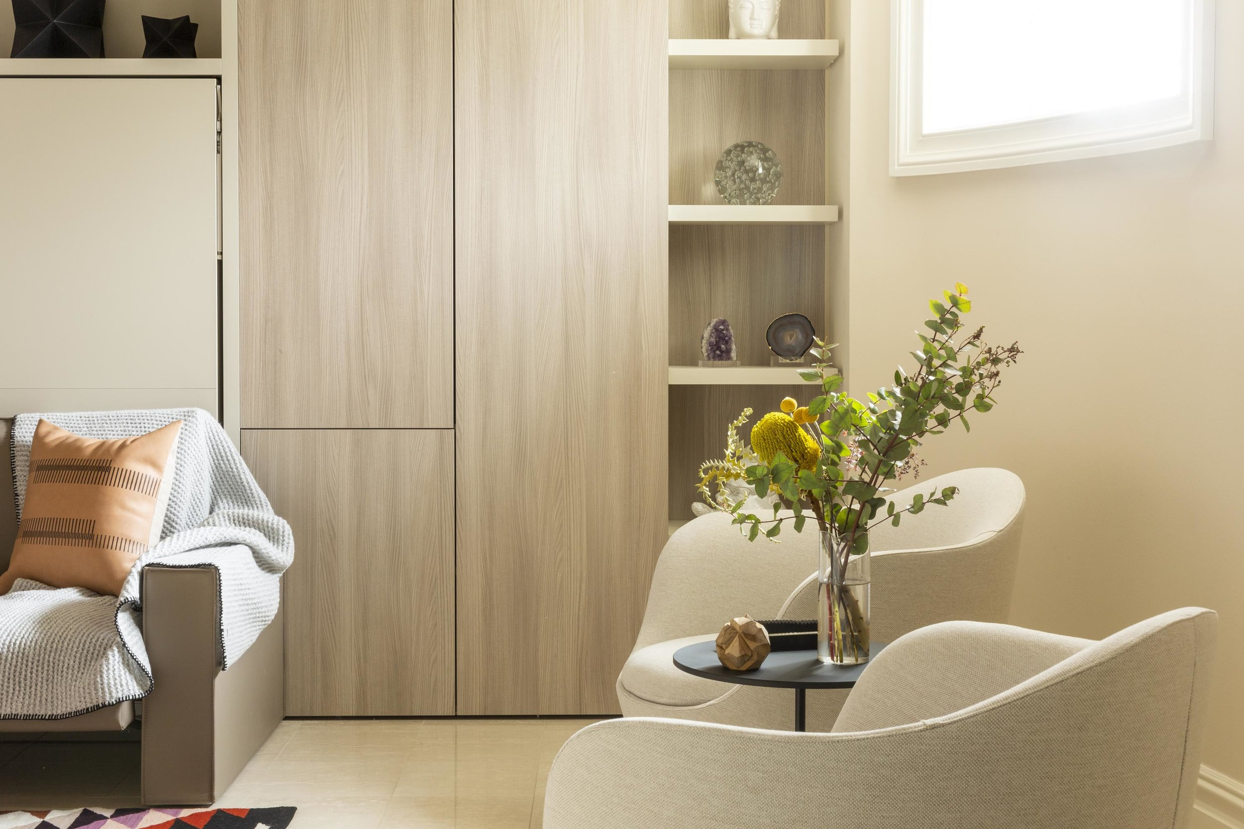 A room with wooden cabinet, armchair and flowers on a clear glass