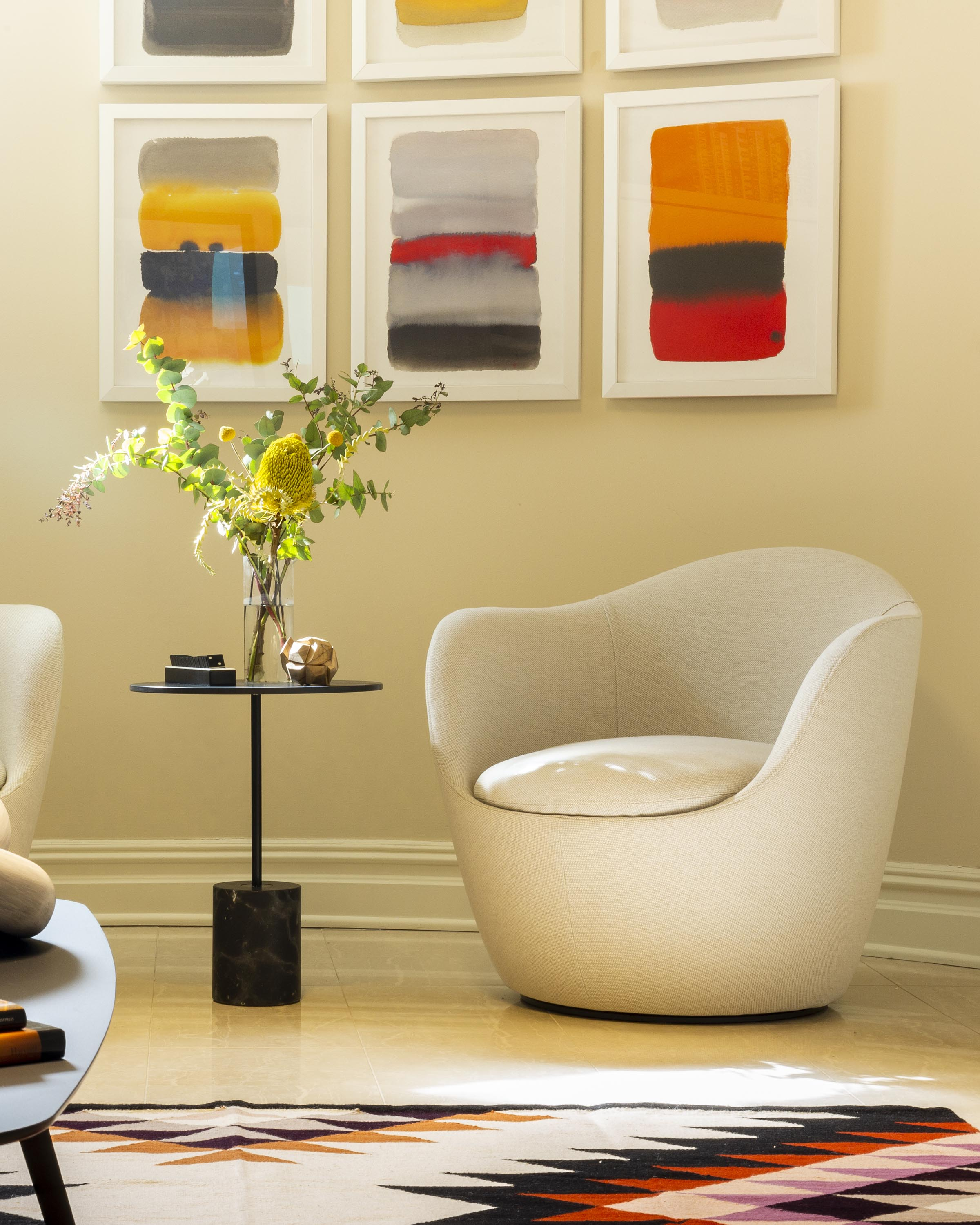 A room with a round table, flowers on a clear glass, armchair and artwork on the wall