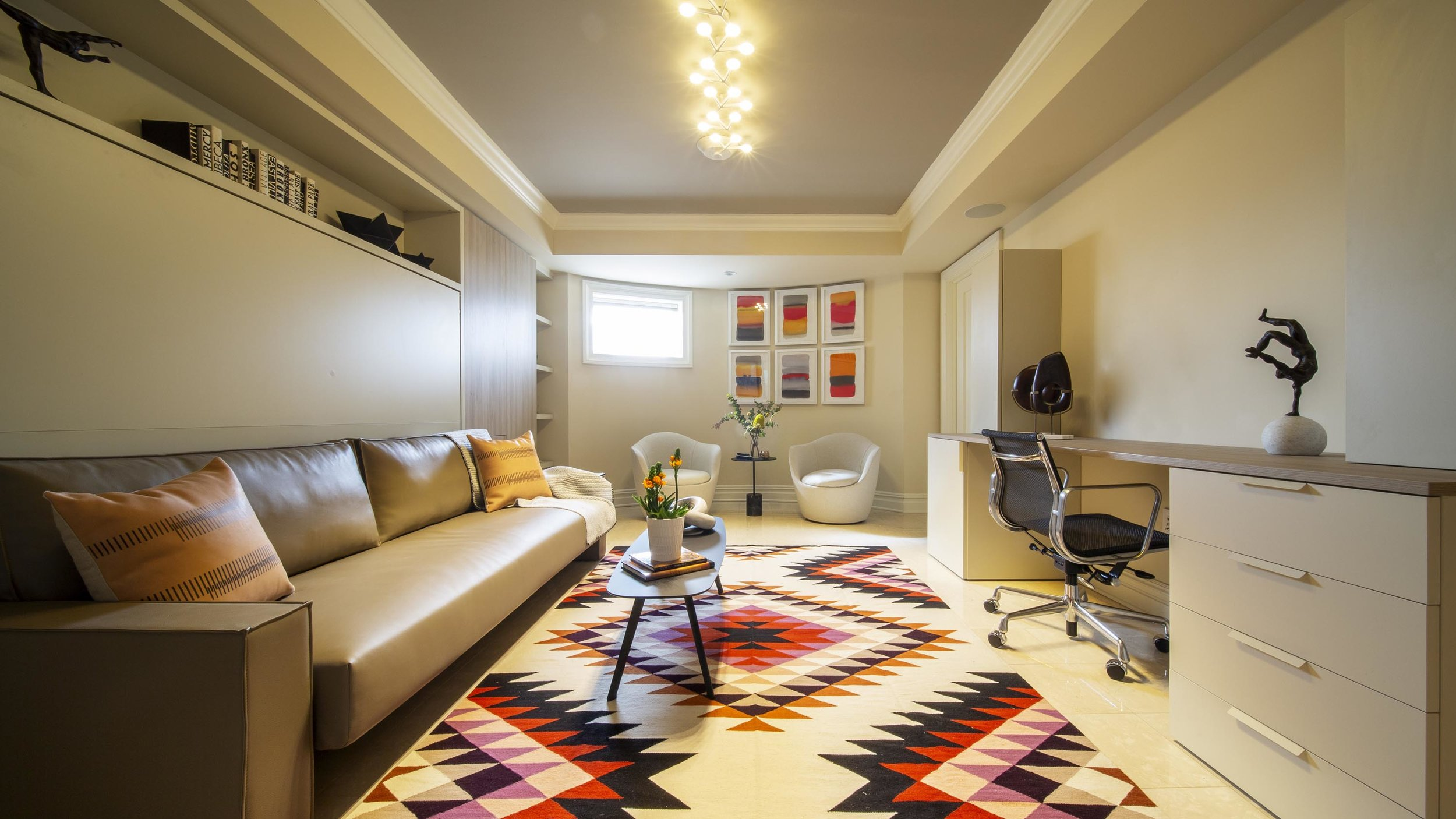 A room with sofa, office chair, abstract texture carpet, white chairs, modern ceiling lights and frames on the wall
