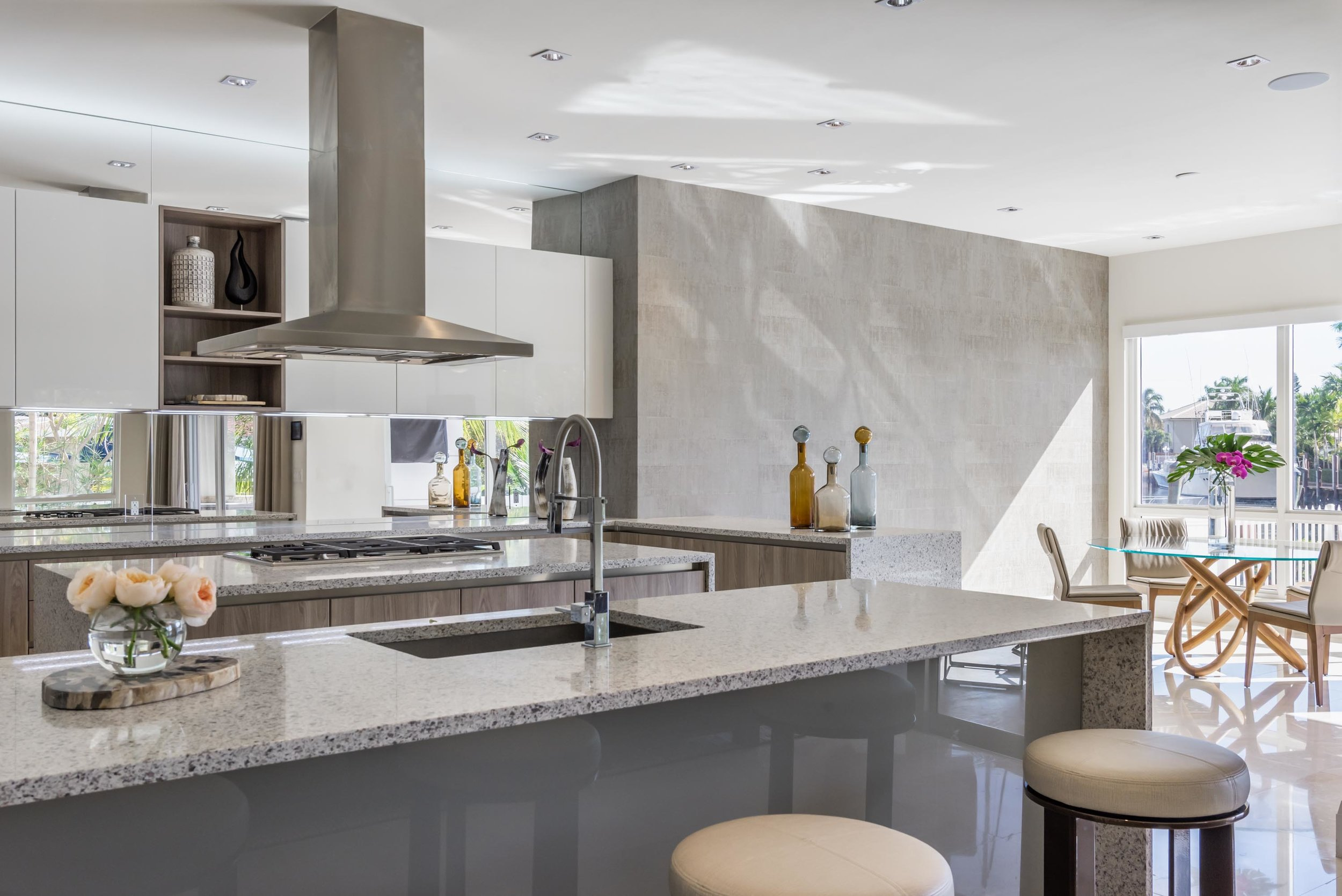 Waterfront modern kitchen area with ceramic countertop, bar stools, exhaust hood, ceramic tile floor and cabinet