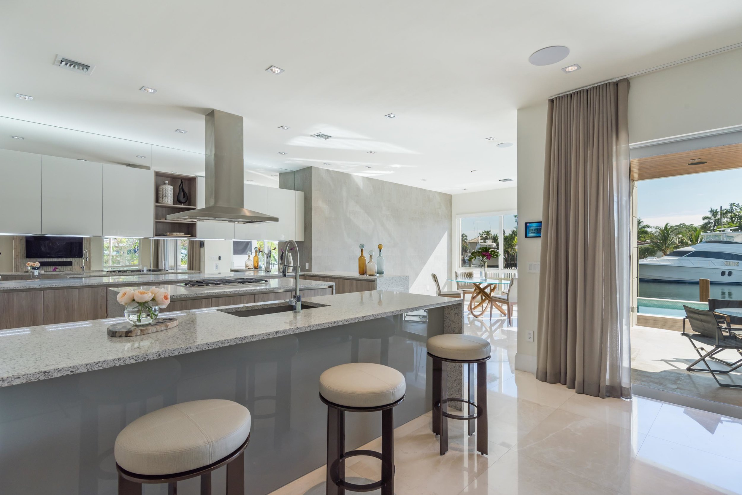 Waterfront modern kitchen area with ceramic countertop, curtain, bar stools, exhaust hood, ceramic tile floor and cabinet
