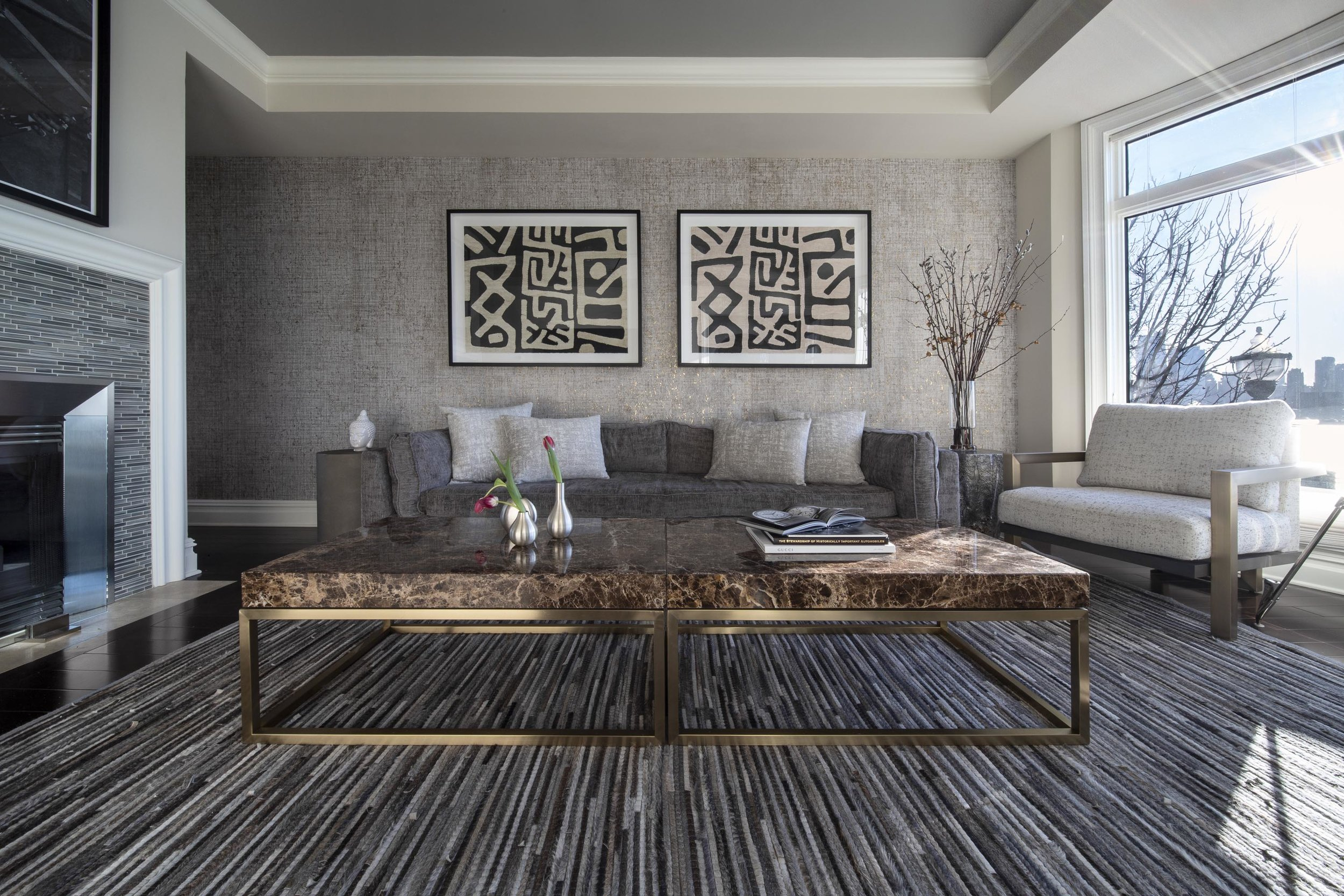 Living room with modern wallpaper and carpet, ceramic top center table, sofa and artwork on the wall