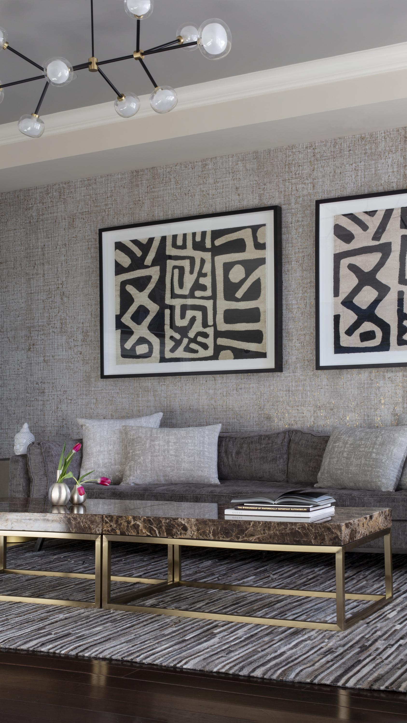 Living room with center table, sofa, custom chandelier and artworks on the wall