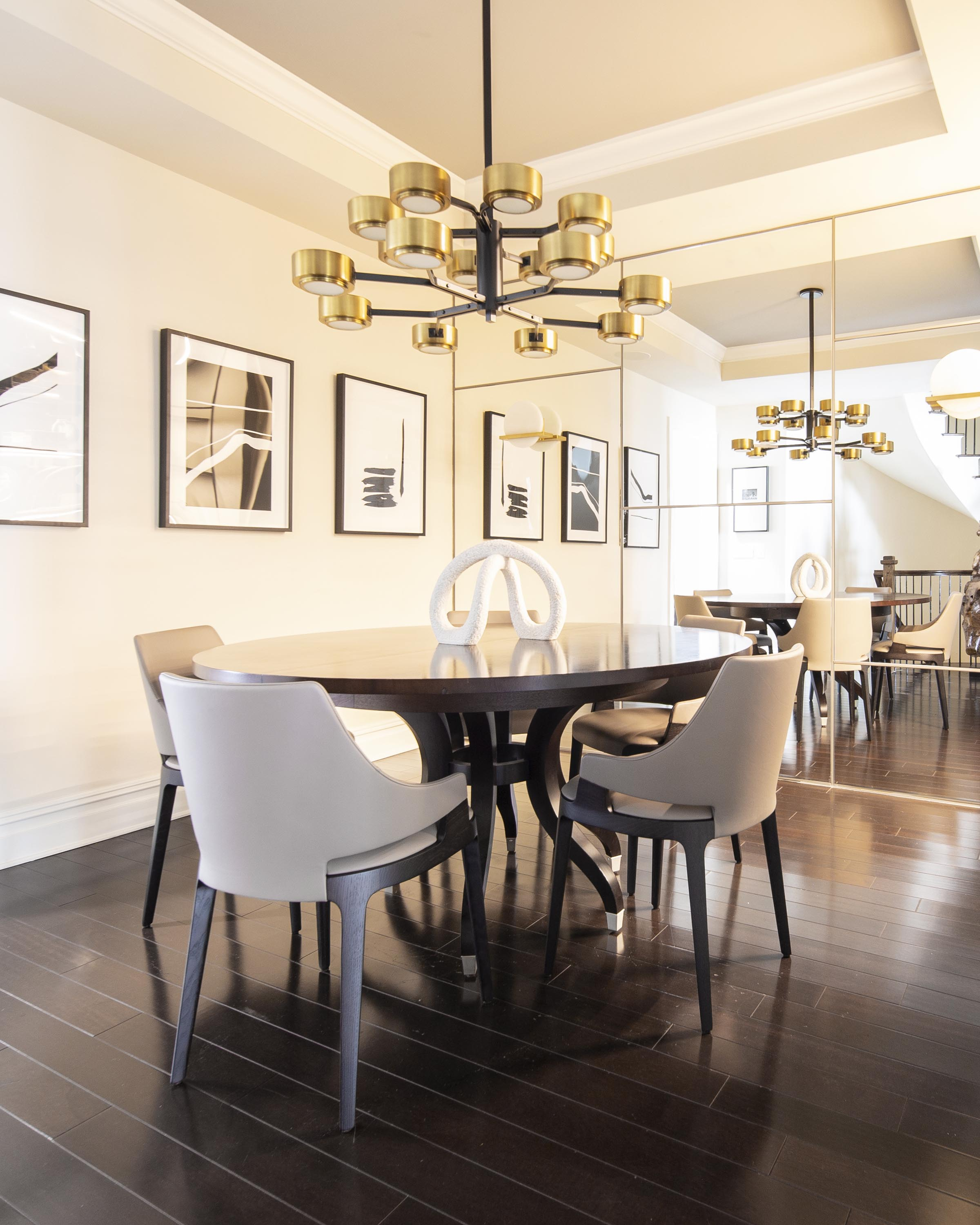 Dining room with round wooden table, chairs, custom chandelier, hardwood floor and artworks on the wall