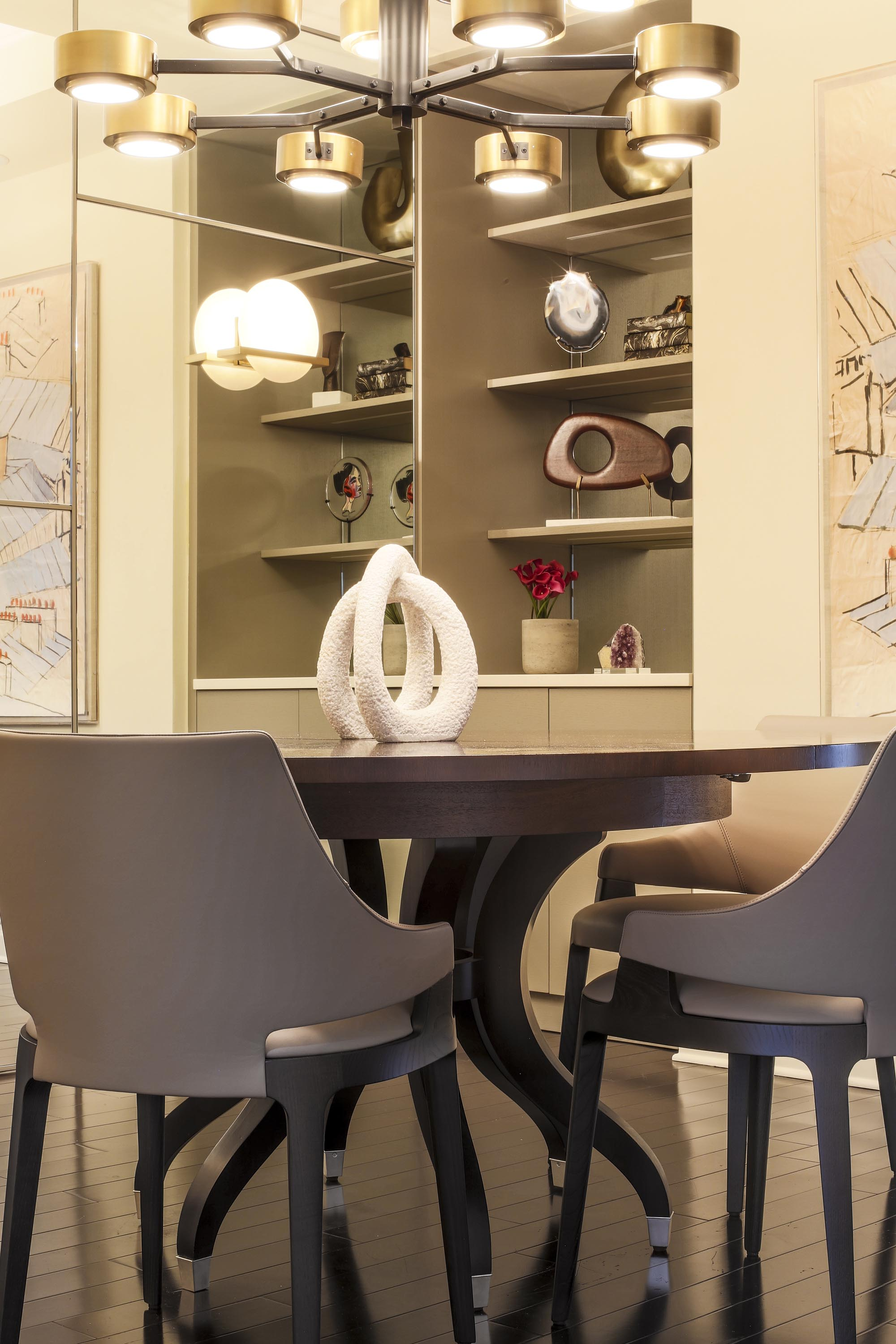 Dining room with built-in cabinetry, round table, chairs and a custom chandelier