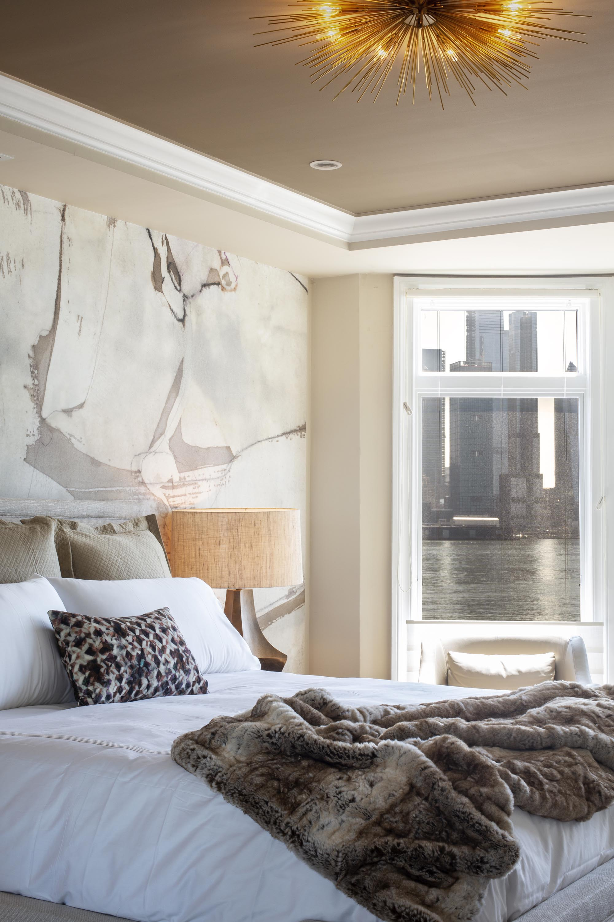 Bedroom with bed, set of pillows, table lamp, modern wallpaper and a white window
