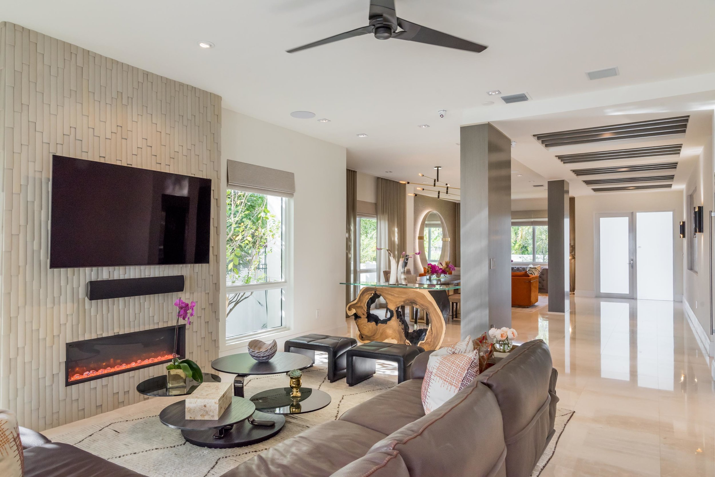 Living room with sofa, chairs, round tables, fireplace, smart tv on wall, ceiling beams and ceiling fan