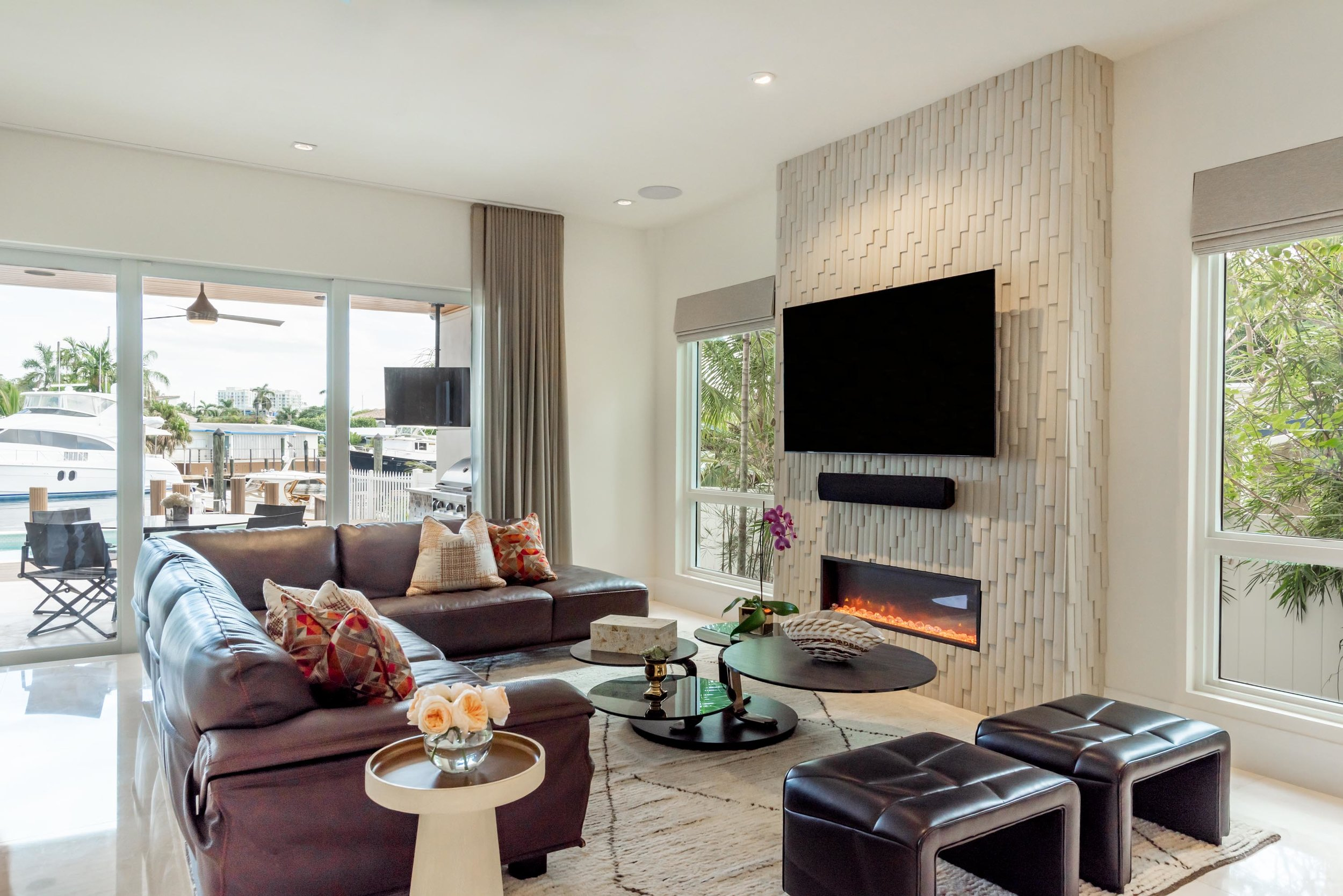 Living room with coastal view, sofa, round tables, chairs, fireplace, smart tv on wall and a custom wall