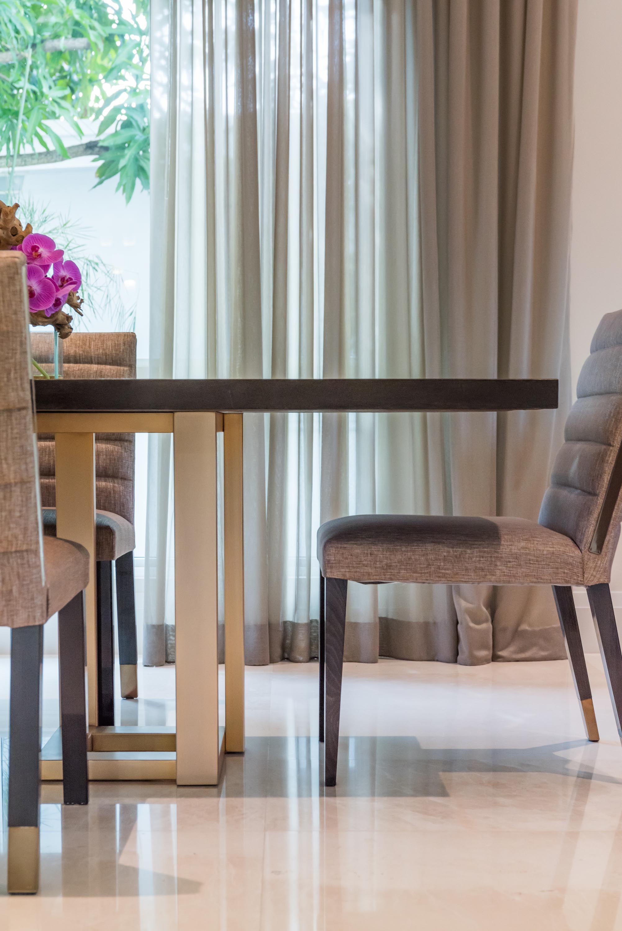 Dining room detail with wooden table and soft seat chairs