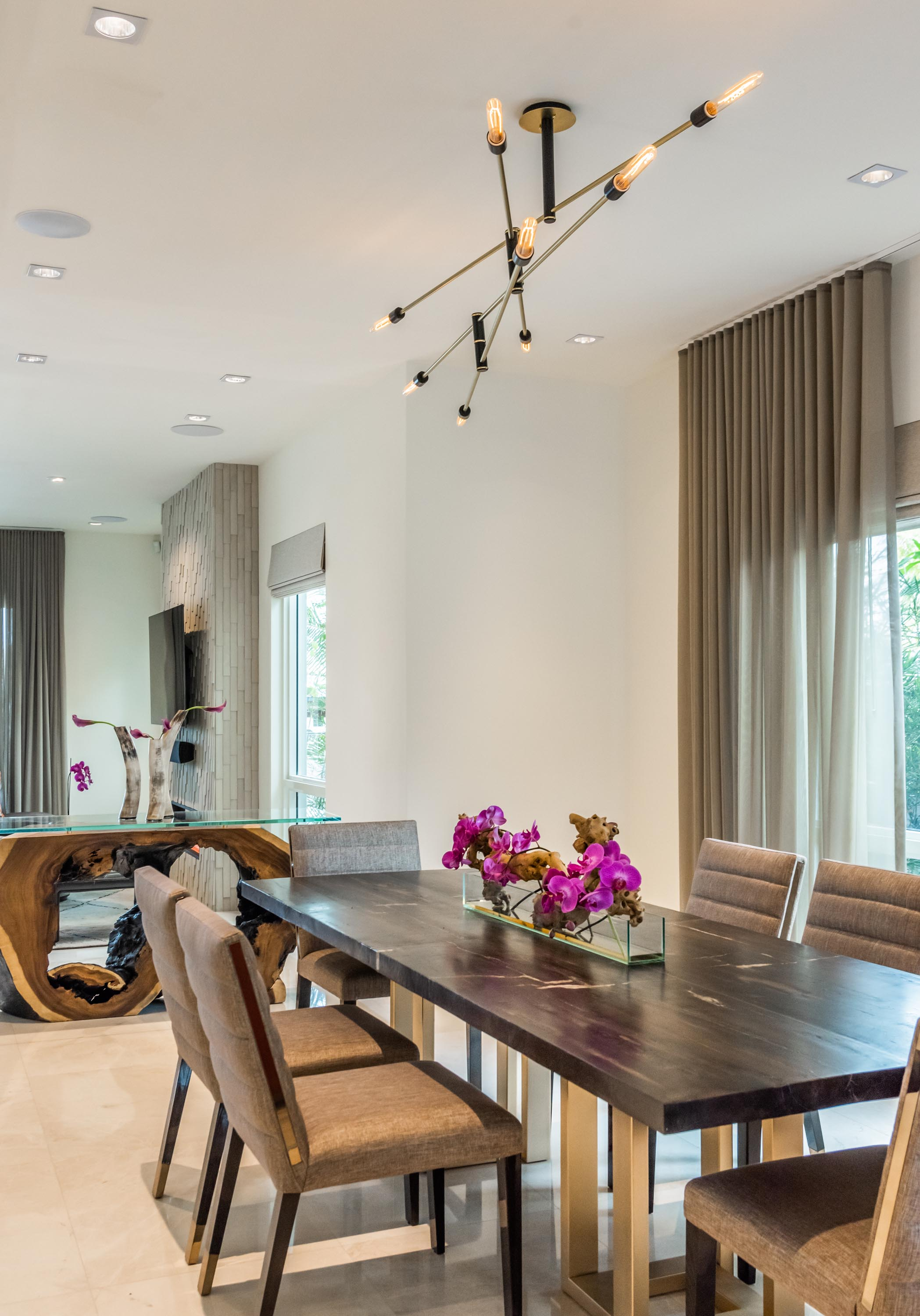 Dining room with wooden table, soft seat chairs and custom ceiling lamps