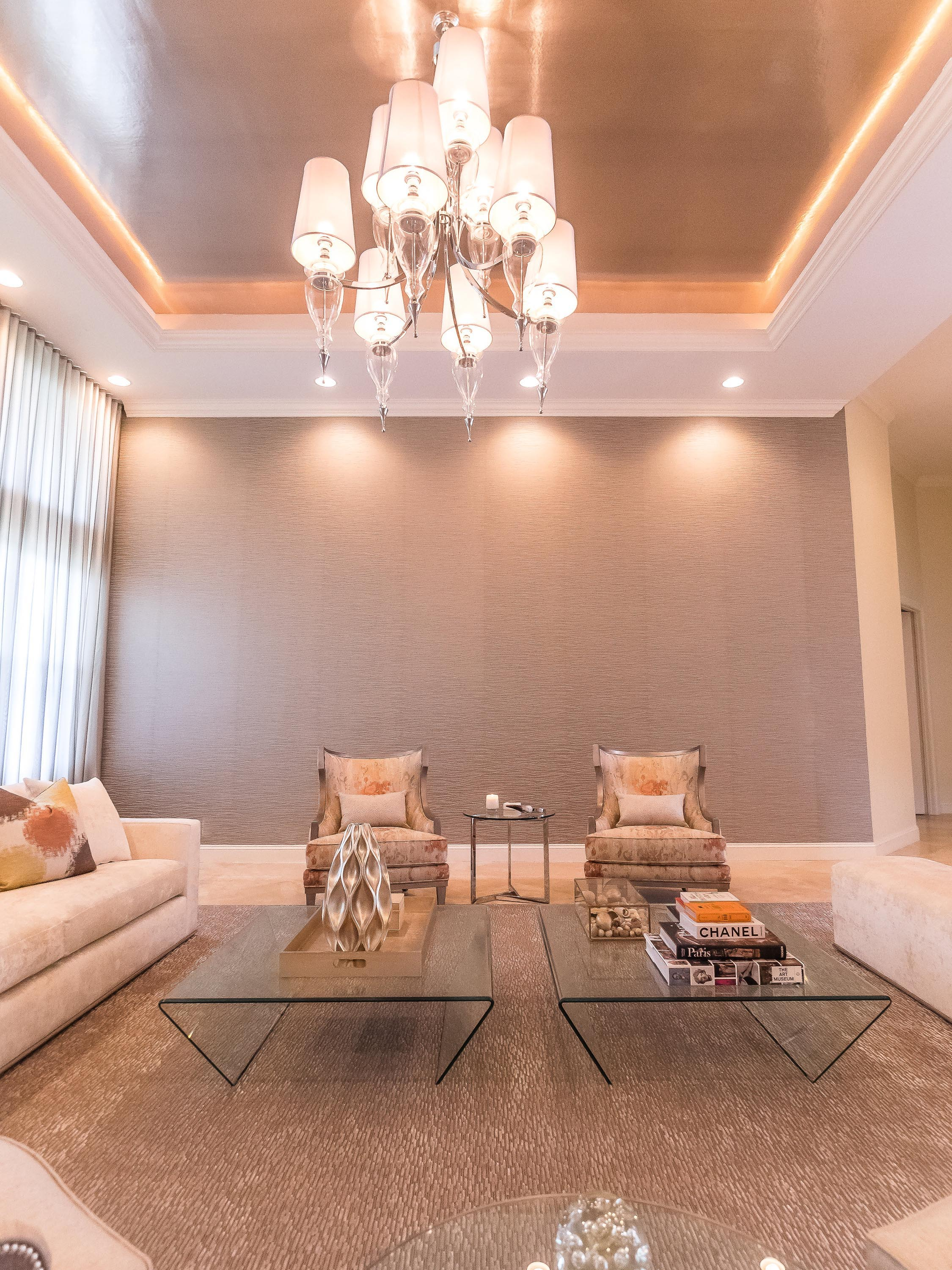 Living room with armchairs, sofa, carpet, custom glass tables and ceiling lamps