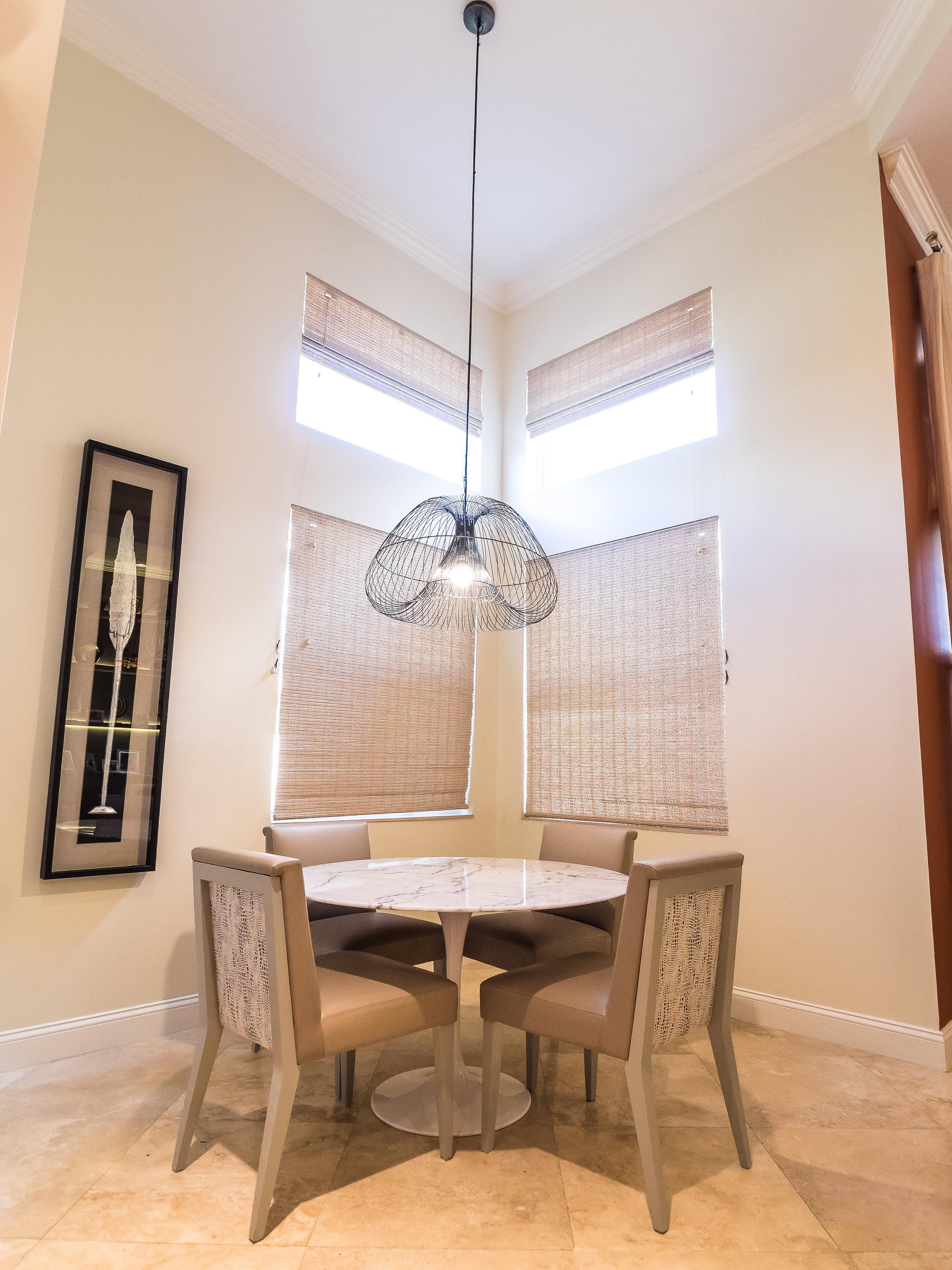 Dining room with a round table, soft seat chairs, artwork on the wall and custom ceiling lamp
