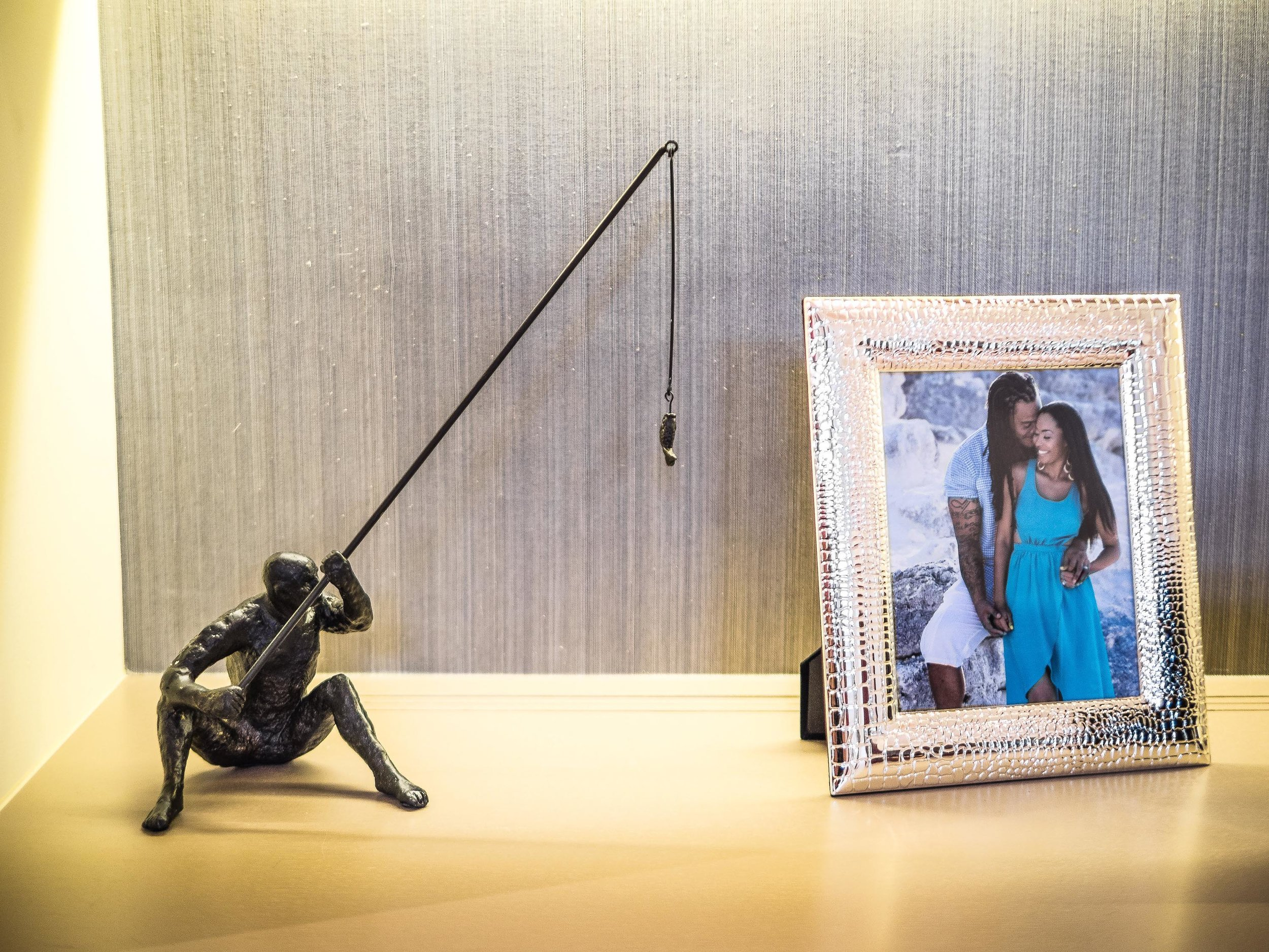 A shelf with couple picture frame and a figurine