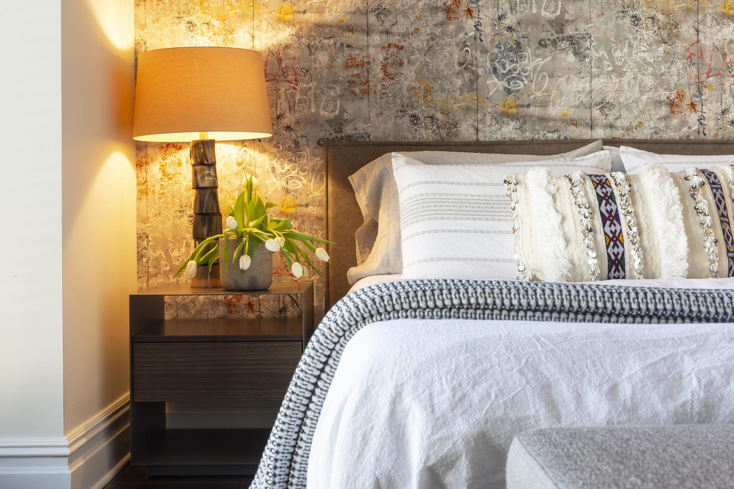 Bedroom with bed, bedside table, table lamp, flowers and custom wallpaper