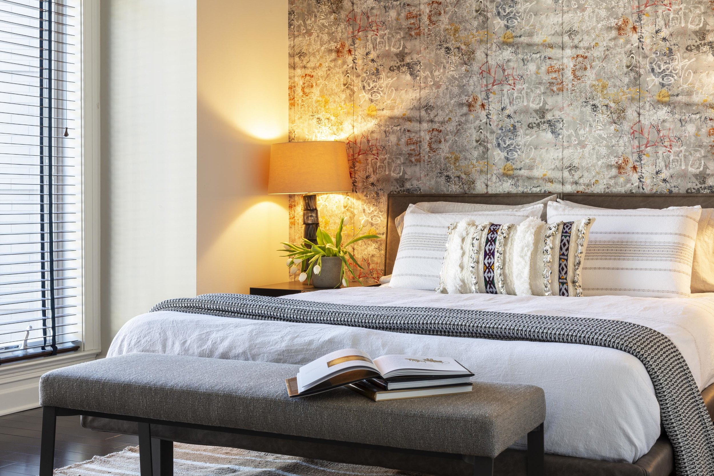 Bedroom with bed, bed bench, table lamp and custom wallpaper