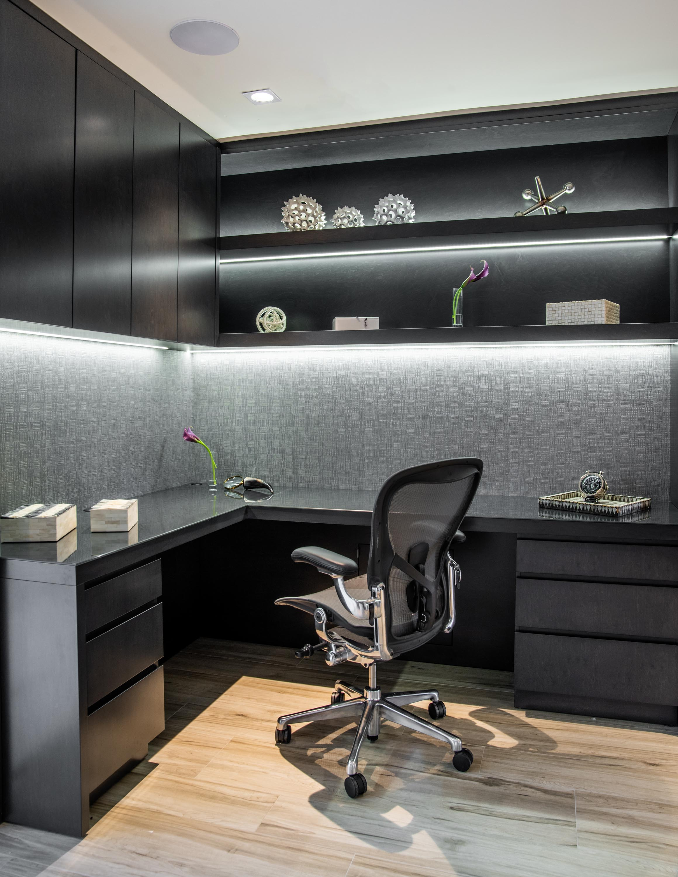 Home office with office chair, hardwood floor and refined custom cabinetry