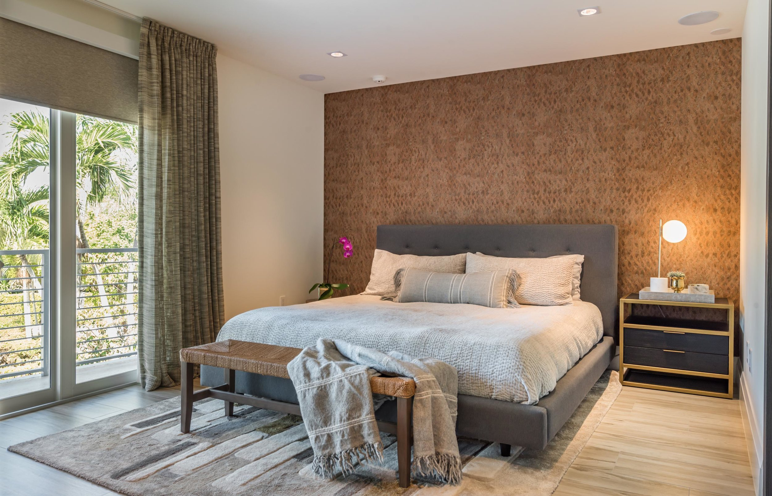 Bedroom with balcony, bed, bed bench, bedside drawer, study lamp, hardwood floor, carpet, and an accent wall