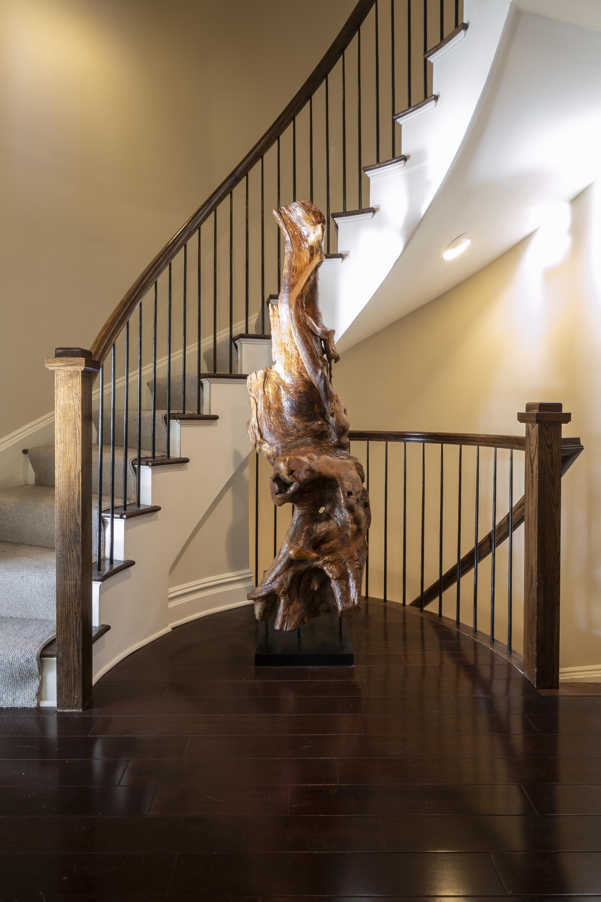 House interior with hardwood floor, staircase and a wooden sculpture