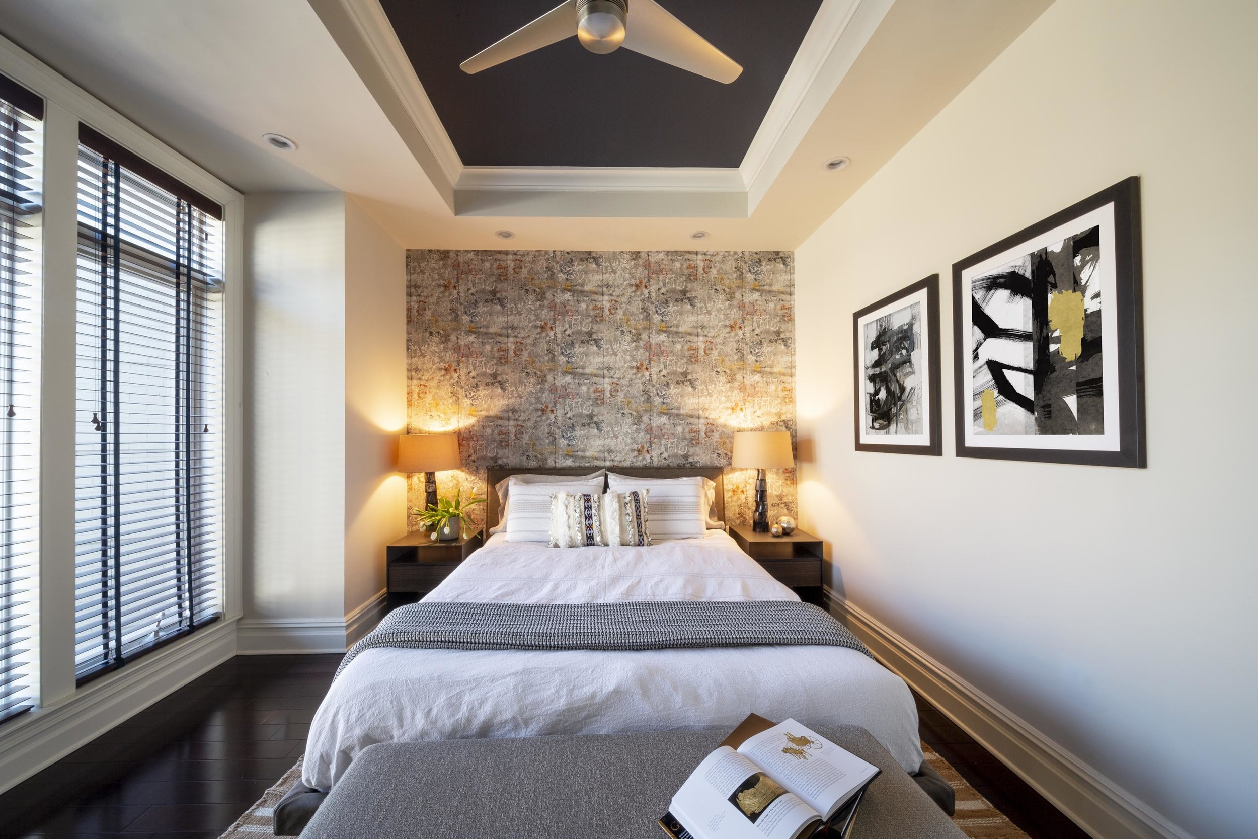 Bedroom with bed, bed bench, bedside tables, table lamps, artwork on the wall, ceiling fan, window with window blinds and hardwood floor