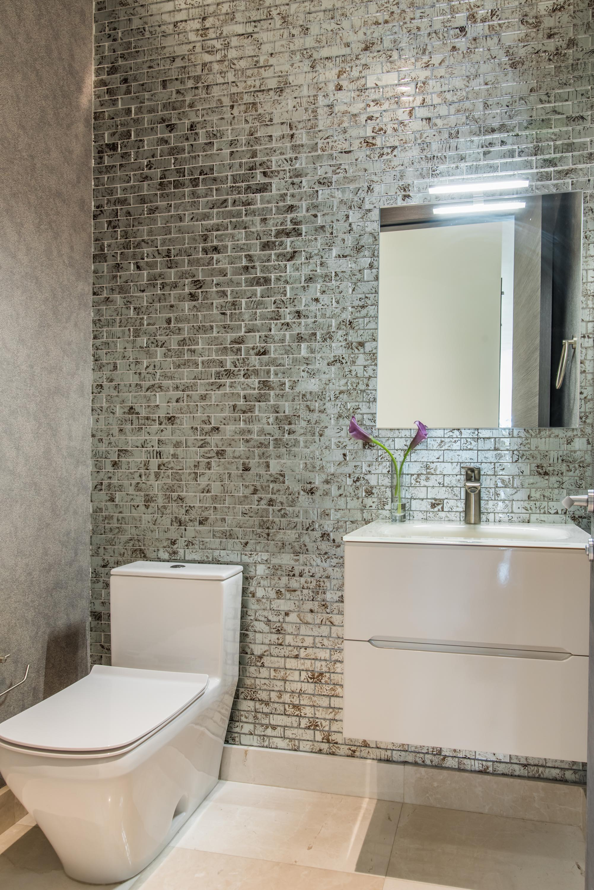 Comfort room with toilet bowl, accent glass tile wall and modern wallpaper