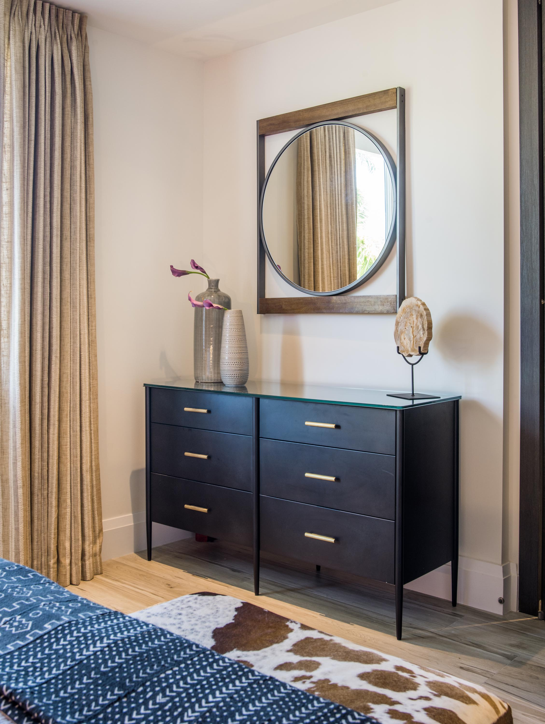 Bedroom with wooden drawer, round mirror on the wall, custom accessories and a hardwood floor