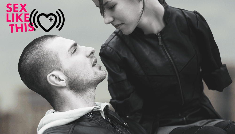 Image Description: Closeup shot of a couple looking deeply into each other's eyes. Person with no arms wears leather jacket. They have wispy bangs and are sitting on top of their partner, who is wearing a hoodie and has a shaved head. The logo for Sex Like This is included: the words SEX LIKE THIS in bright pink next to black heart with Rx sign surrounded by radio waves. The waves cut through the S in THIS, which is tilted at an angle.
