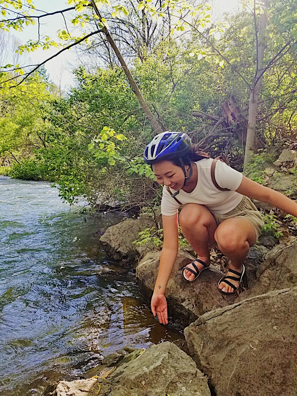 Michelle squatting by a lake with bike helmet..JPG