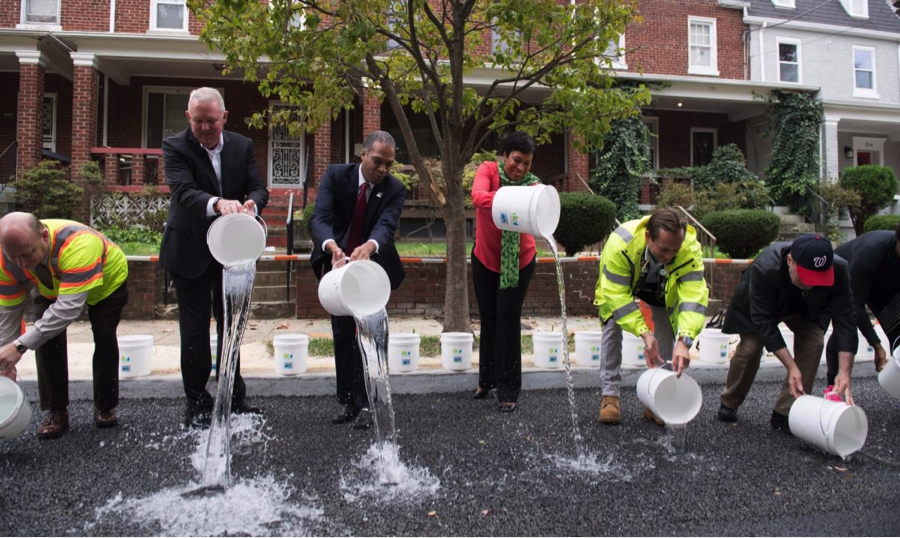 DC Water CEO George Hawkins, Mayor Muriel Bowser and other District leaders pour buckets of water onto permeable pavement to demonstrate the benefits of green infrastructure