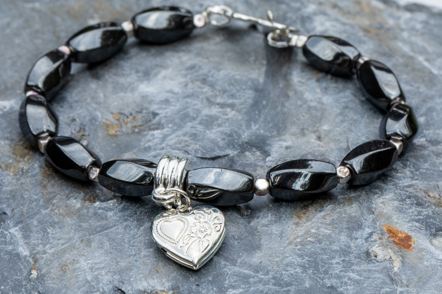 Twisted hematine bracelet with silver plated heart locket - £28