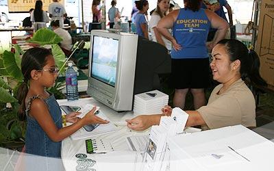 Volunteer Melissa Takushi working the Malama Aina Foundation booth.