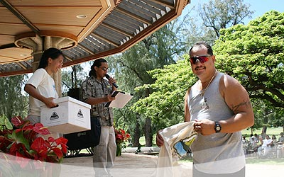 A happy Jason Agliam holding his E Ola Pono t-shirt he has just won in a free drawing sponsored by Mālama 'Āina Foundation