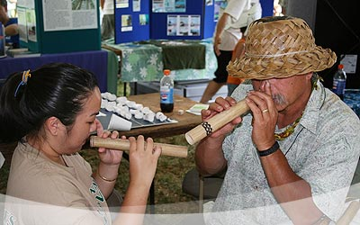 Uncle Calvin Hoe teaching Melissa Takushi how to play the nose flute.
