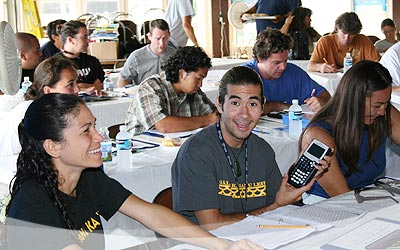 Hakipu'u Learning Center's Ryan McCormack (center) happily displays a TI-84 calculator. To the left is Paepae O He'eia's Kauwila Hanchett and to the right is Hakipu'u Learning Center's Tia Roberts.